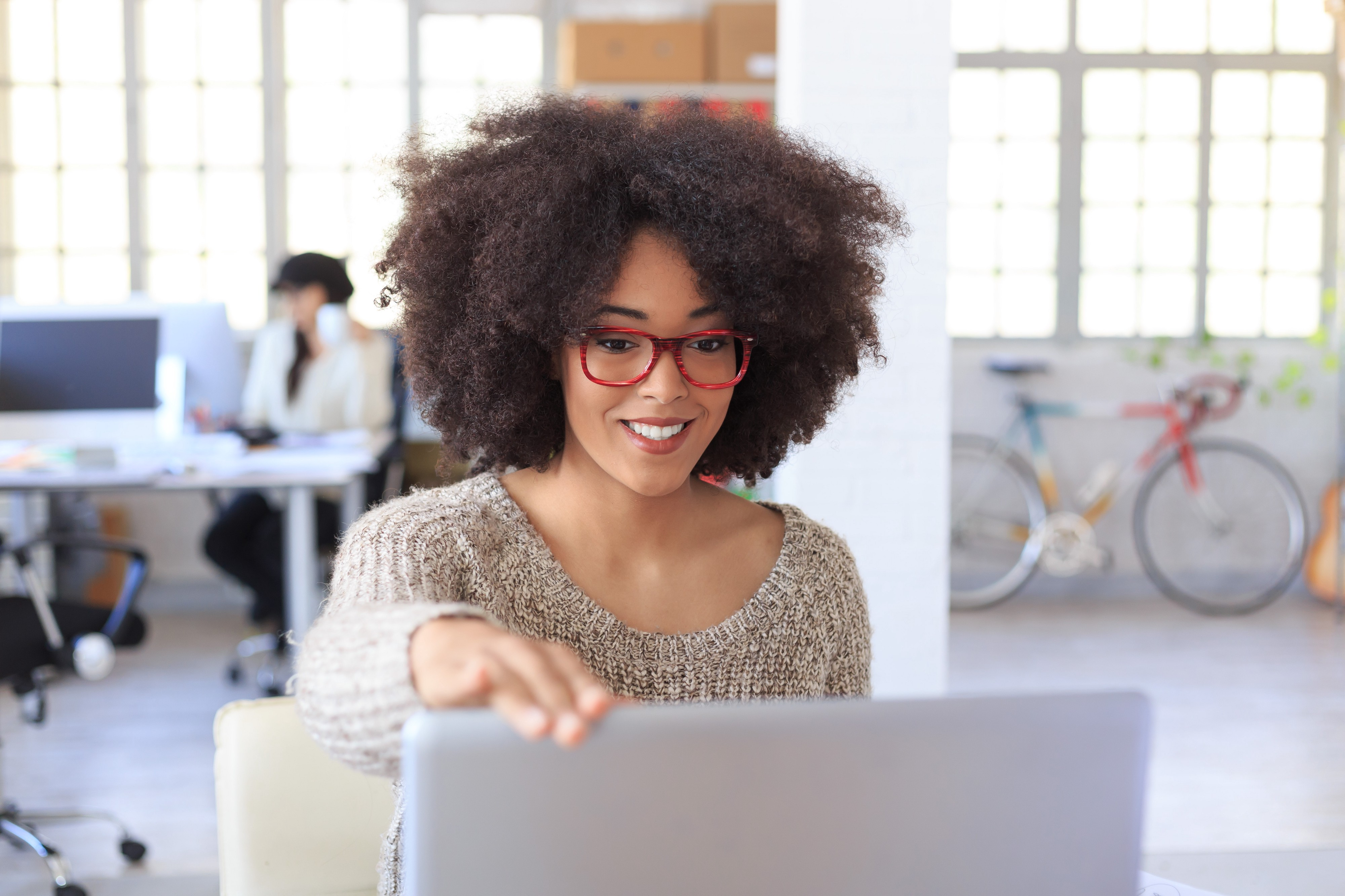 Smiling young woman with red eyeglasses finishing her work at the office and closing her laptop.