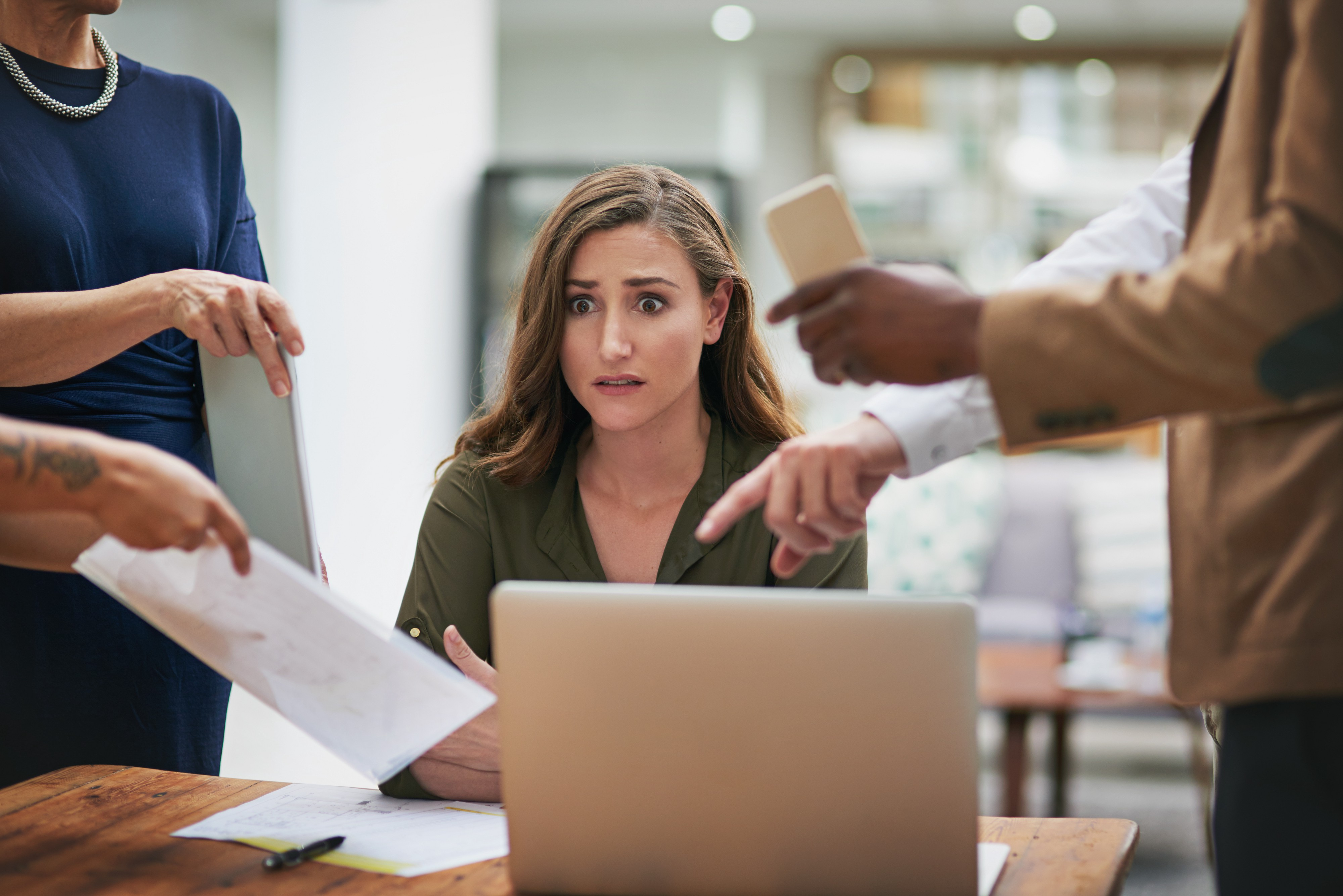 A young business woman looks anxious as her coworkers surround her desk demanding things of her.