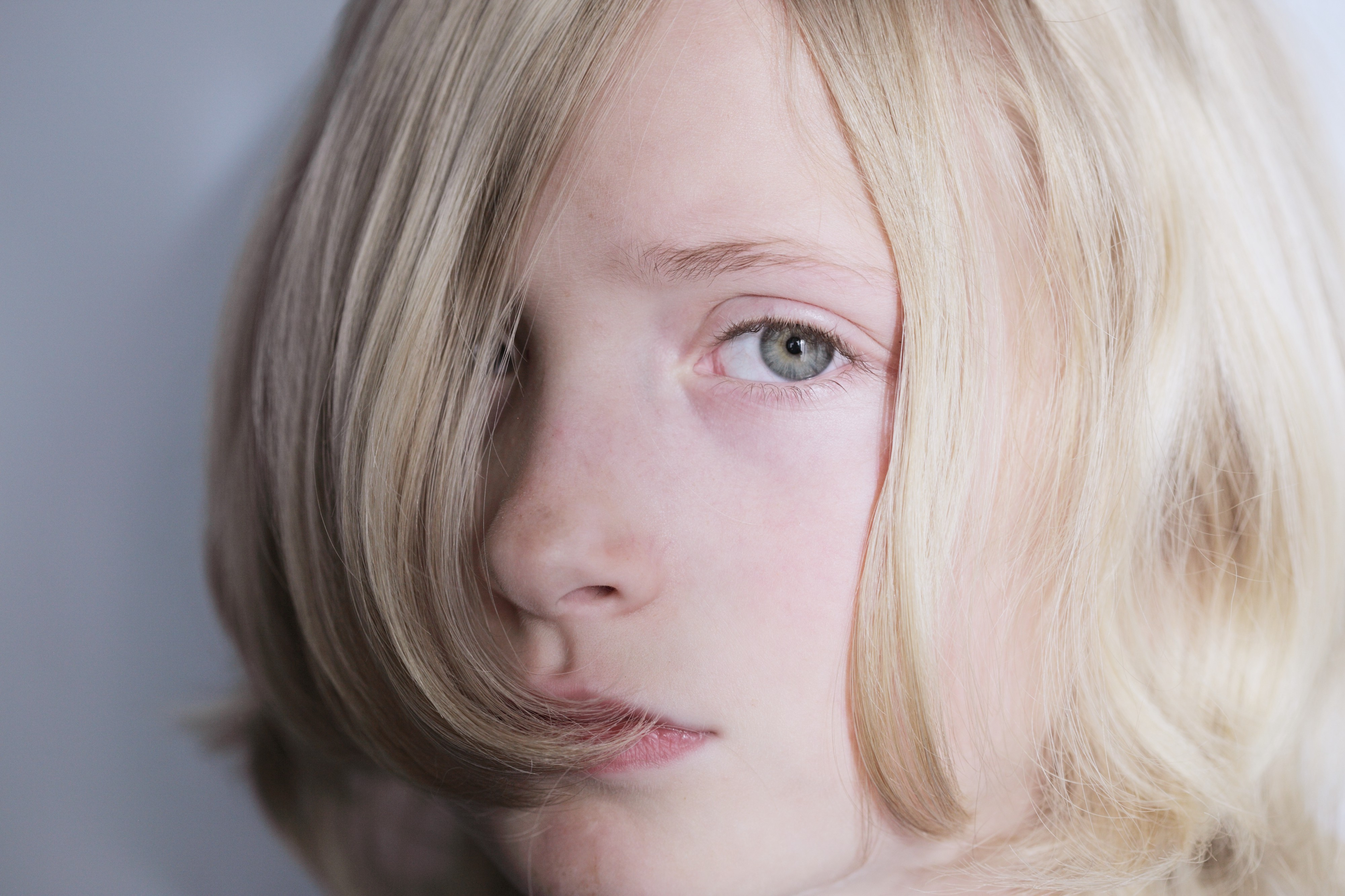 Young person with blond hair covering right eye, looking at camera.