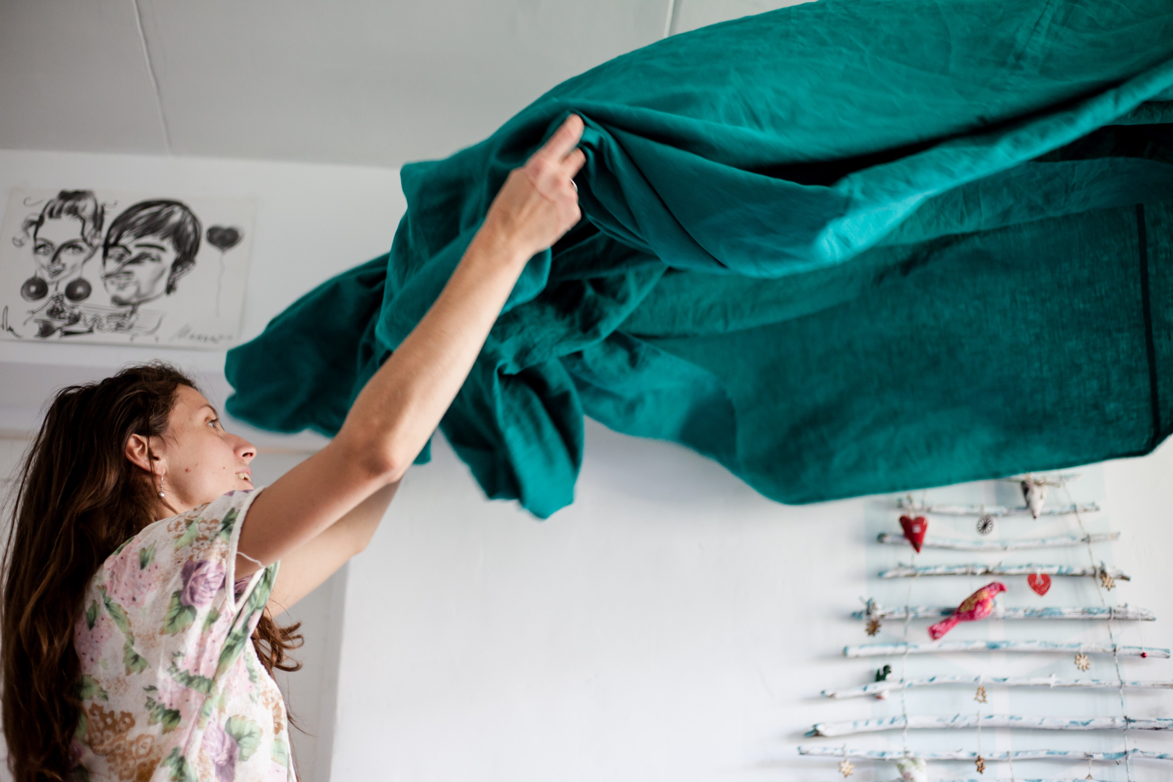 A woman with long brown hair throwing up a turquoise sheet before she makes a bed.