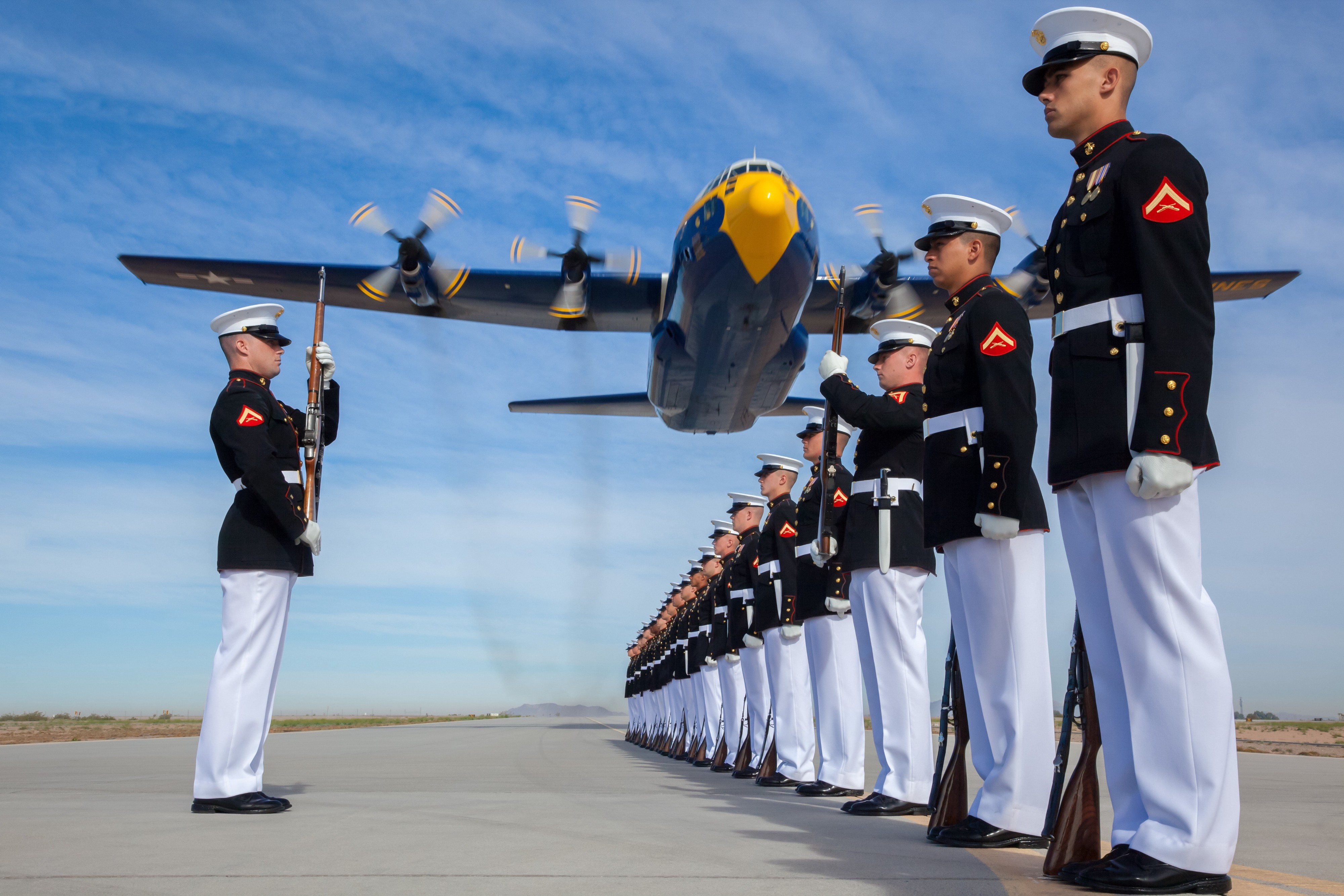 Group of US Marines standing in formation with an airplane flying overhead.