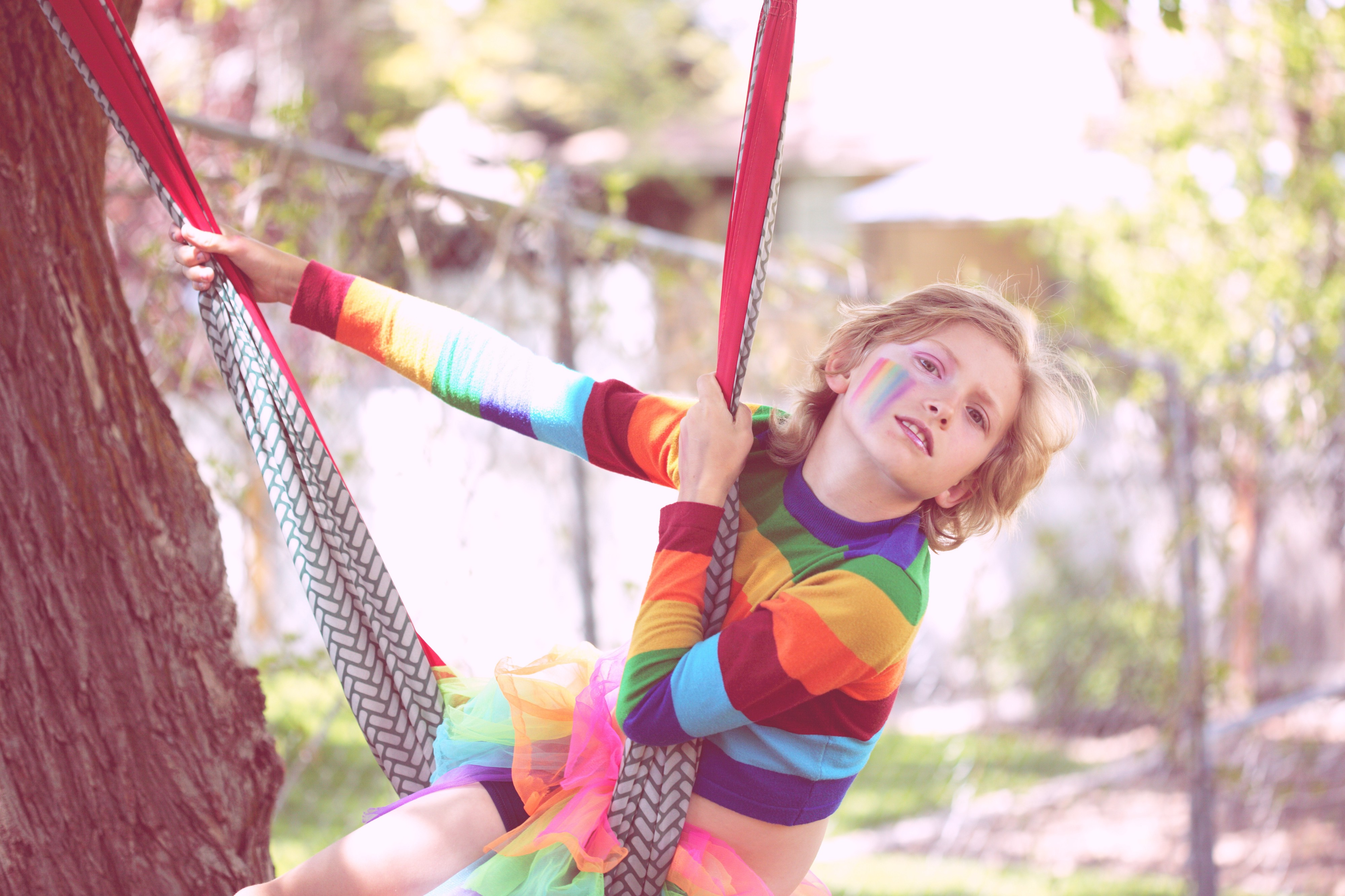 Photo of nonbinary child on swinging on a tree