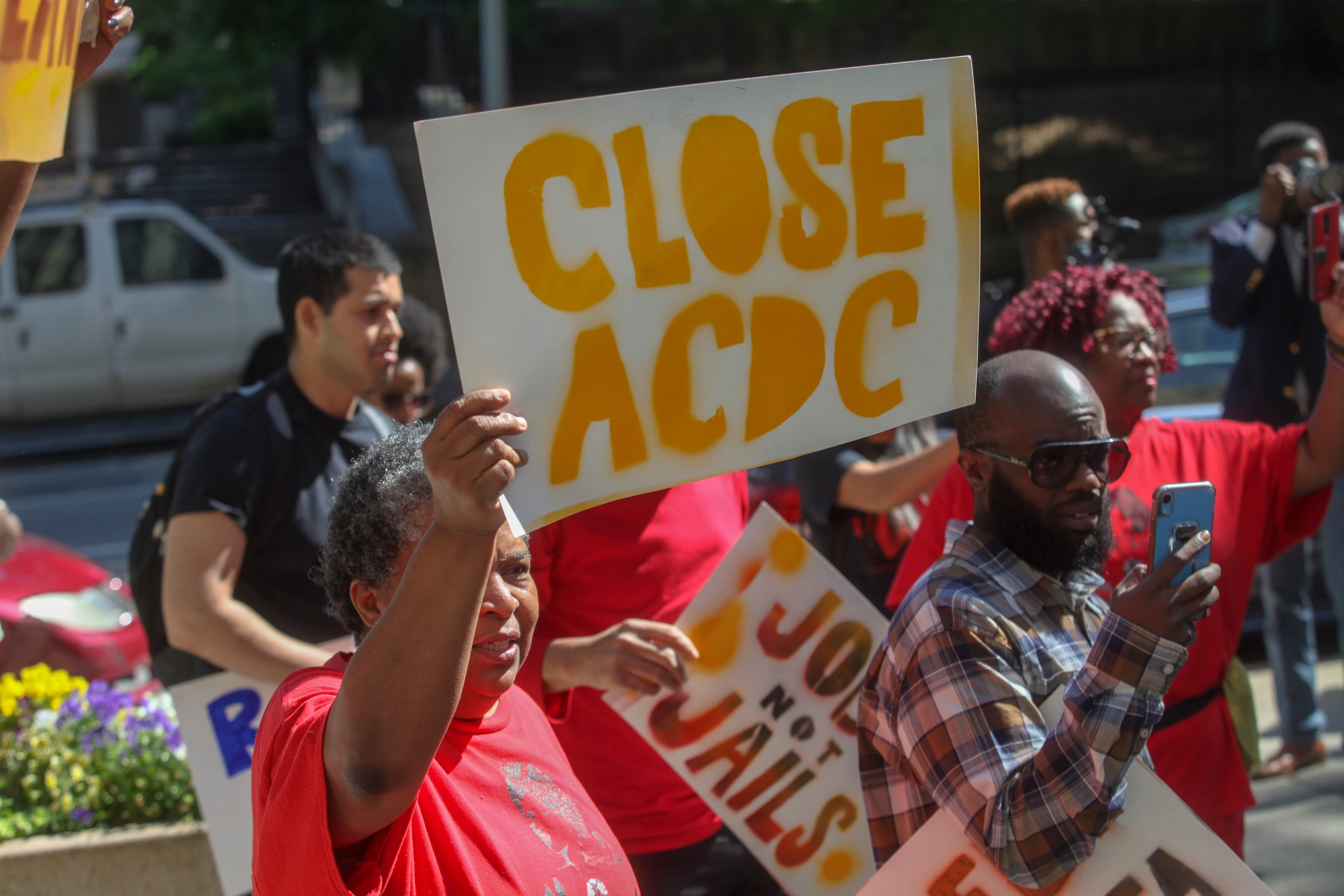 """Organizers stand with red shirts, one woman has sign that says """"Close ACDC"""" and another has a sign that says """"Jobs Not Jails"""""""