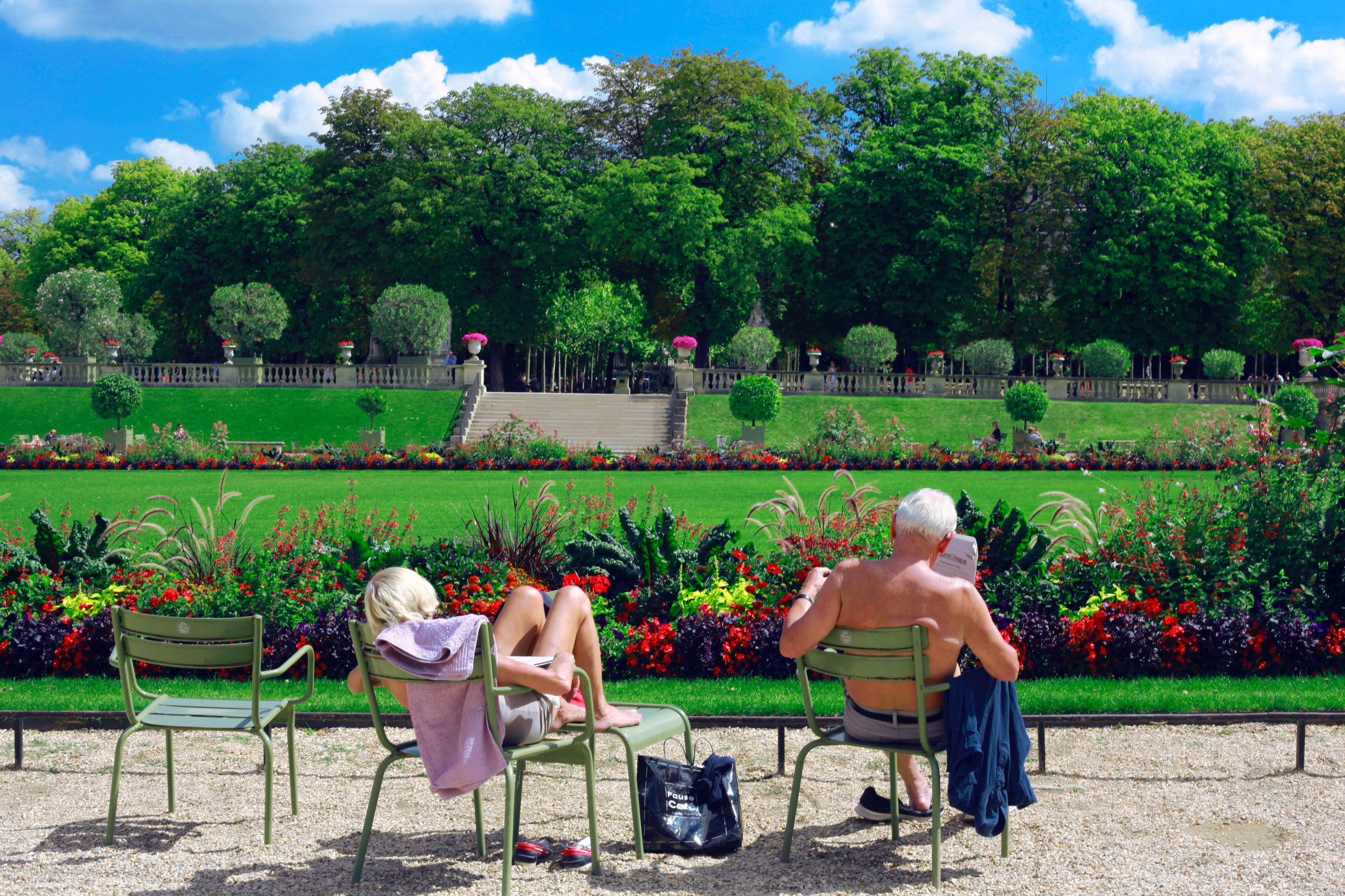 Man and woman sitting on green chairs in a garden