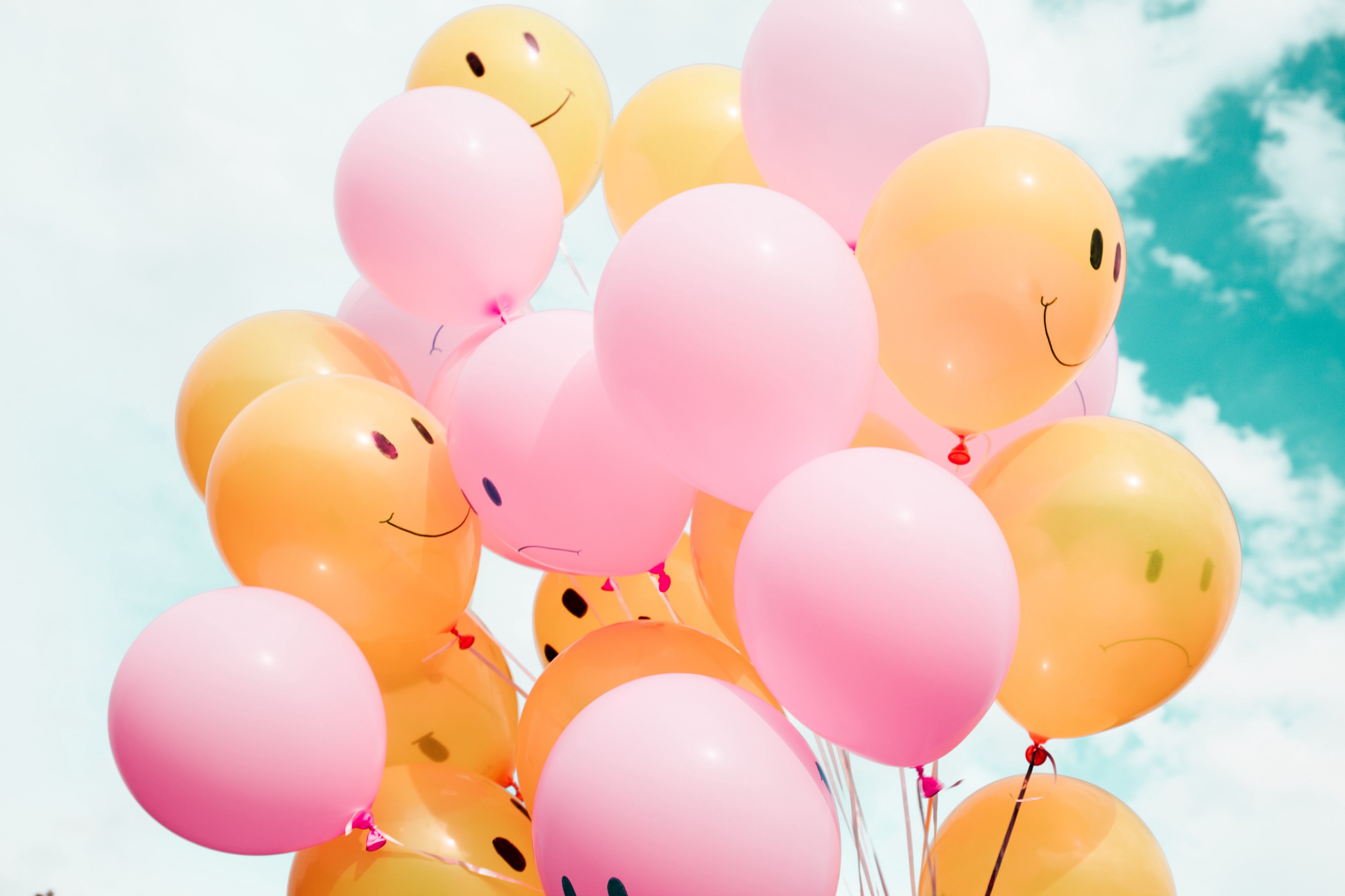 Photo showing a collection of balloons with a sky background. Half of the balloons are yellow with a happy smilie face, the other half are pink with a sad smilie face.