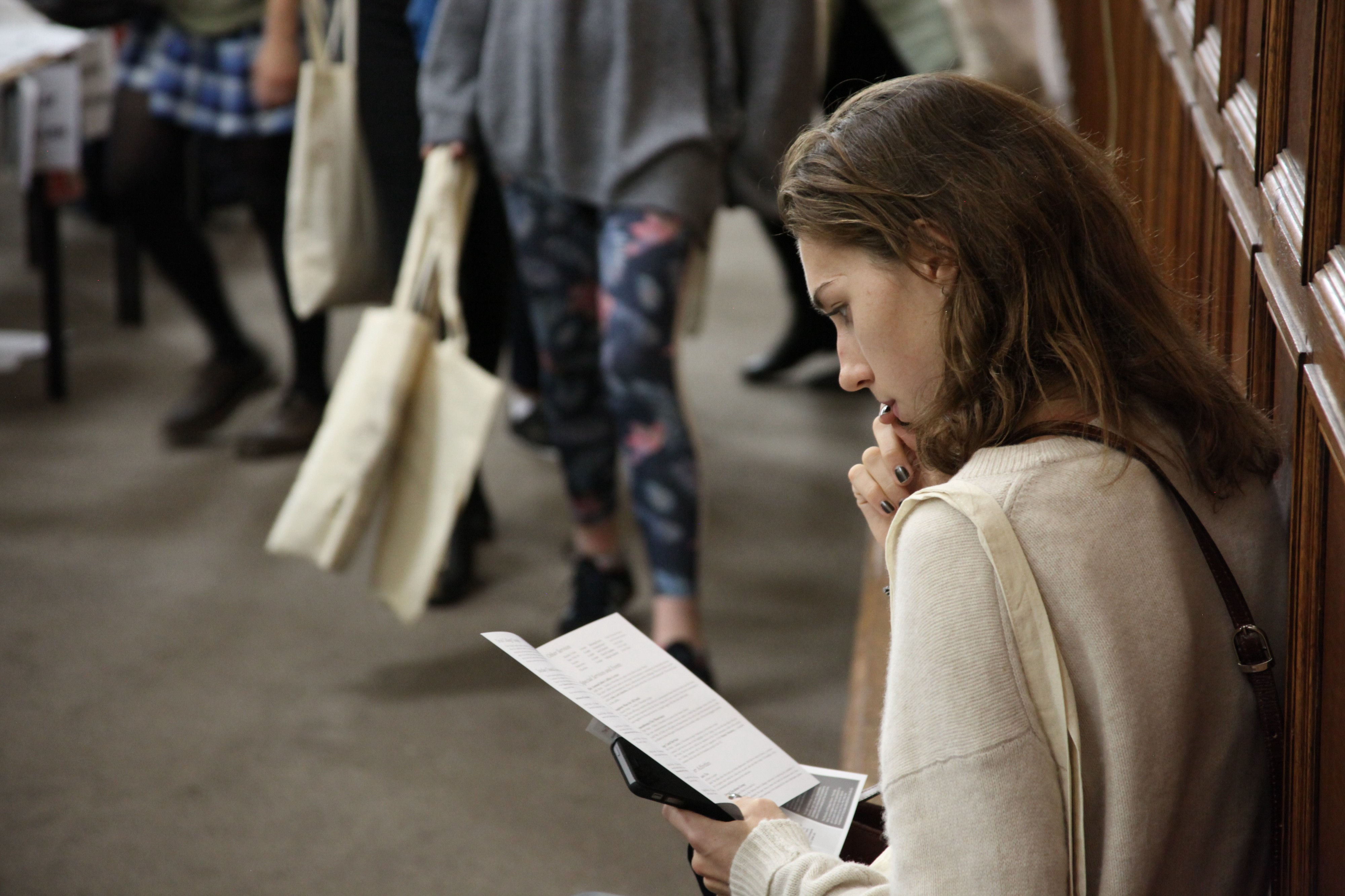 A woman reading a piece of paper.