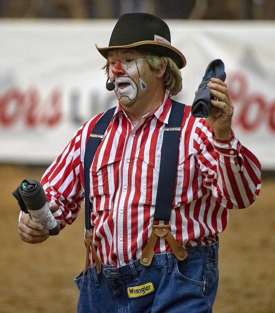 Rodeo clown with face paint in blue suspenders holding up loose Wrangler jeans with red and white striped shirt.