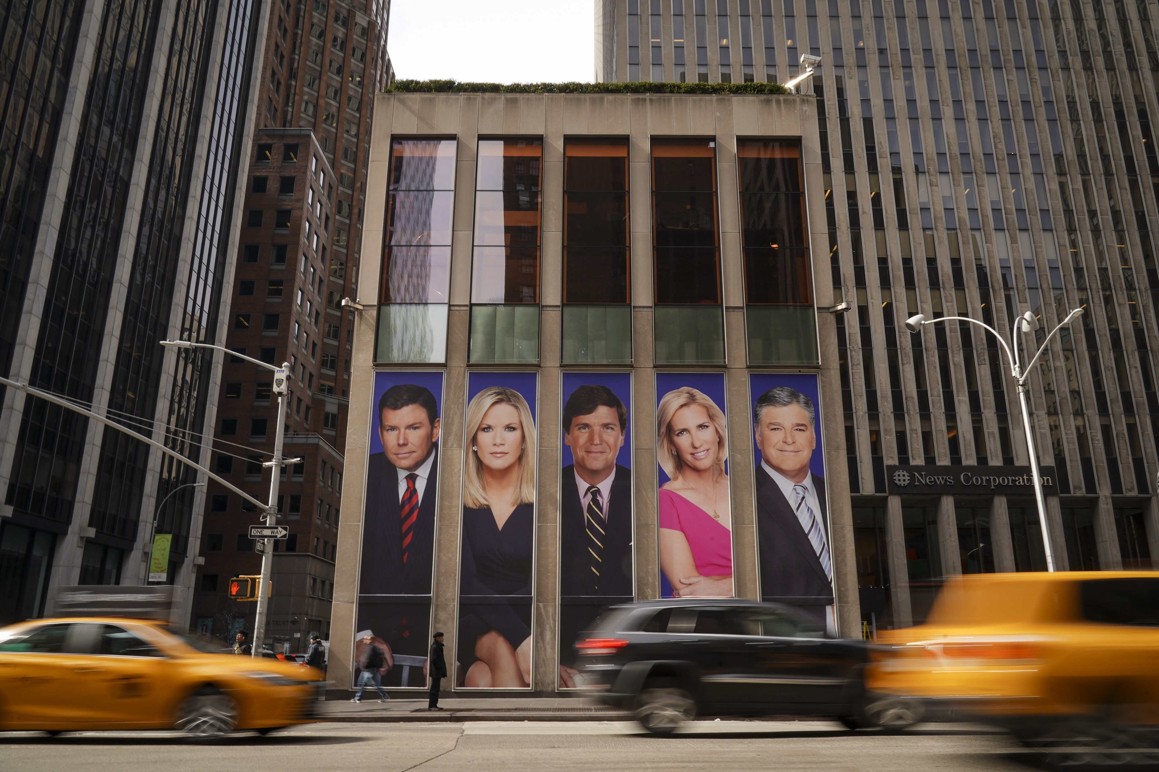 Bret Baier, Martha MacCallum, Tucker Carlson, Laura Ingraham, Sean Hannity as ads on the front of the News Corp building.
