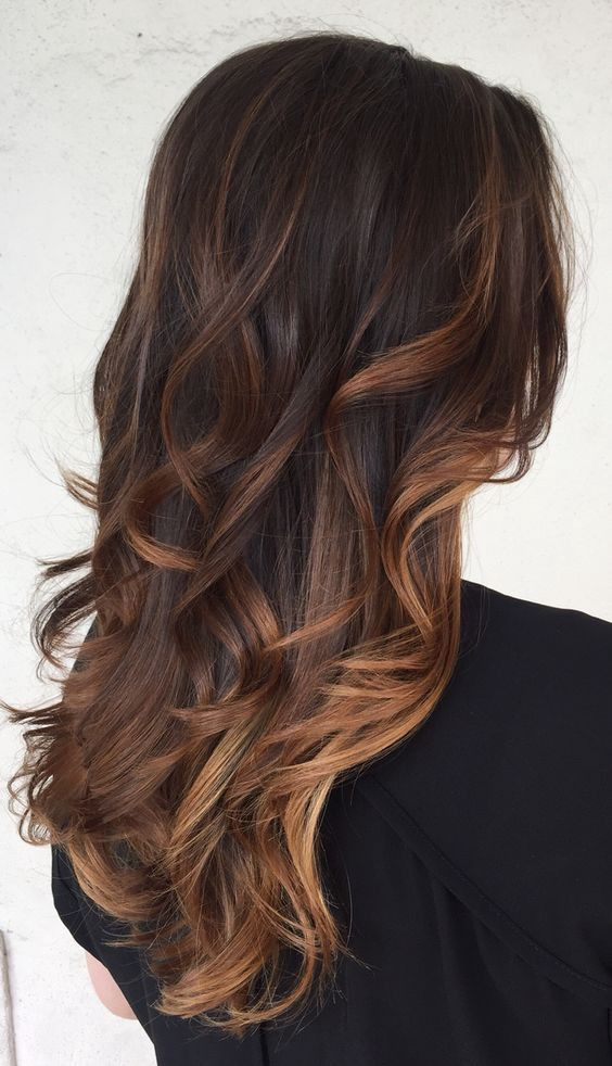 This classy ombre hairstyle uses three different colors: dark brown at the roots, light brown as a transition, and golden blonde at the tips