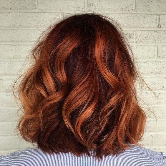 Spruce up your spring look with a burst of red - this short red wavy cut uses both light and dark copper tones