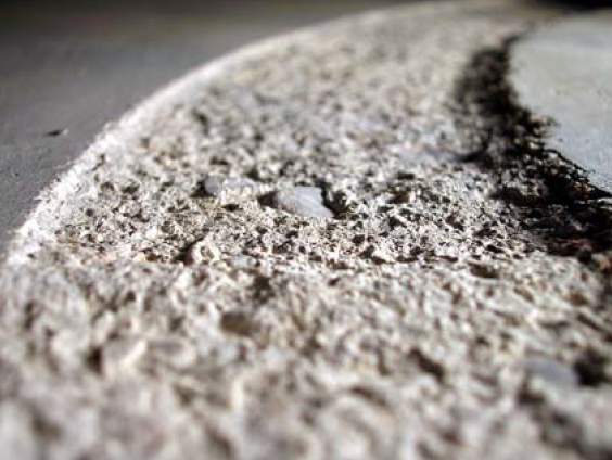 An abrasion test has worn a groove in the concrete slab, showing the aggregate underneath the paste.