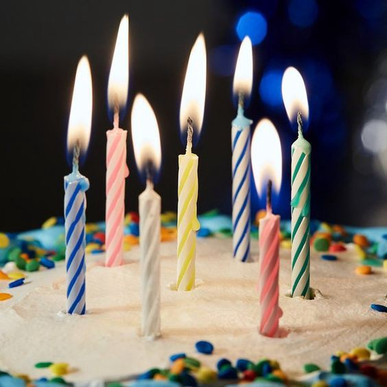 seven lit candles on a birthday cake