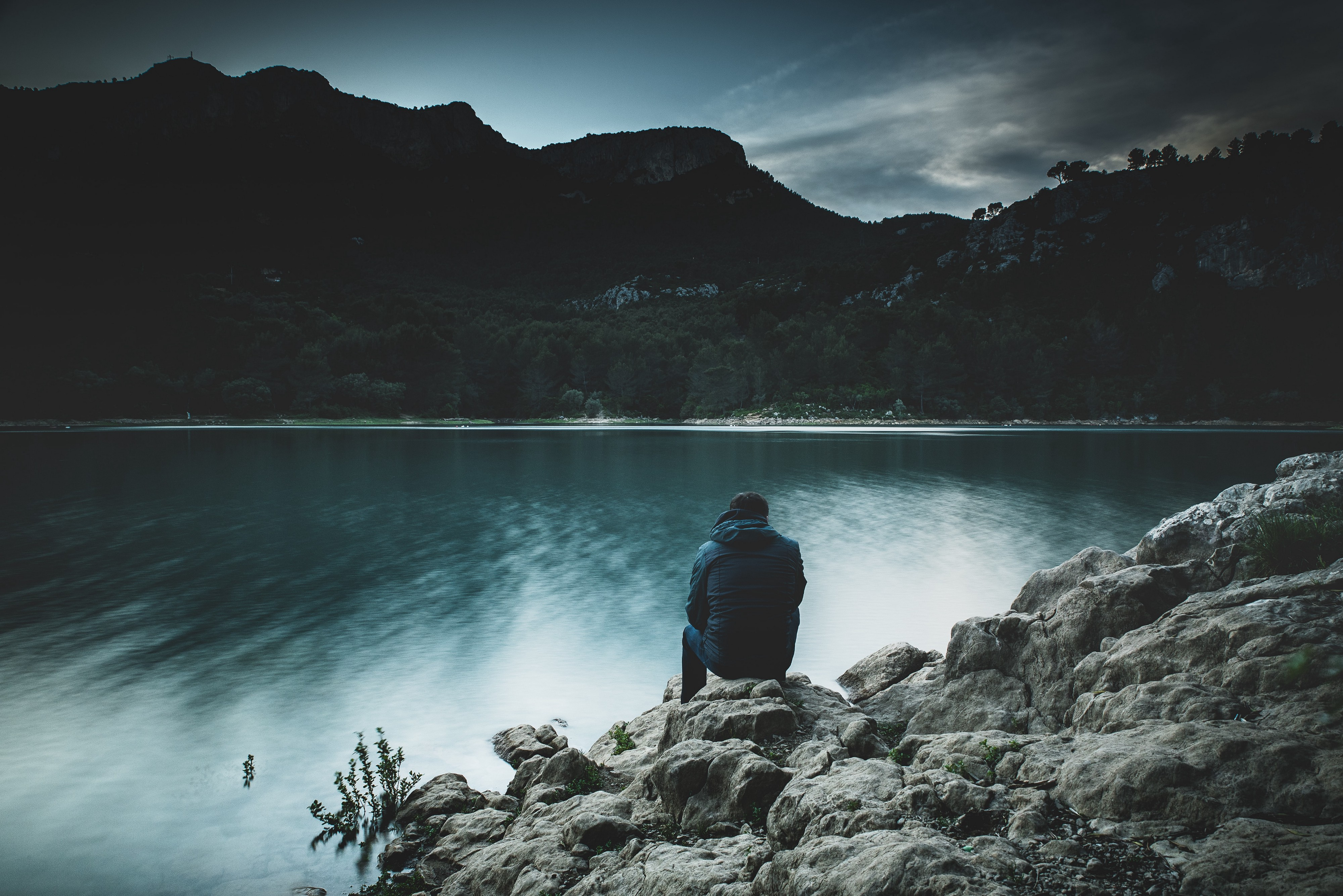 A man sitting alone in silence in front of a lake and mountains.