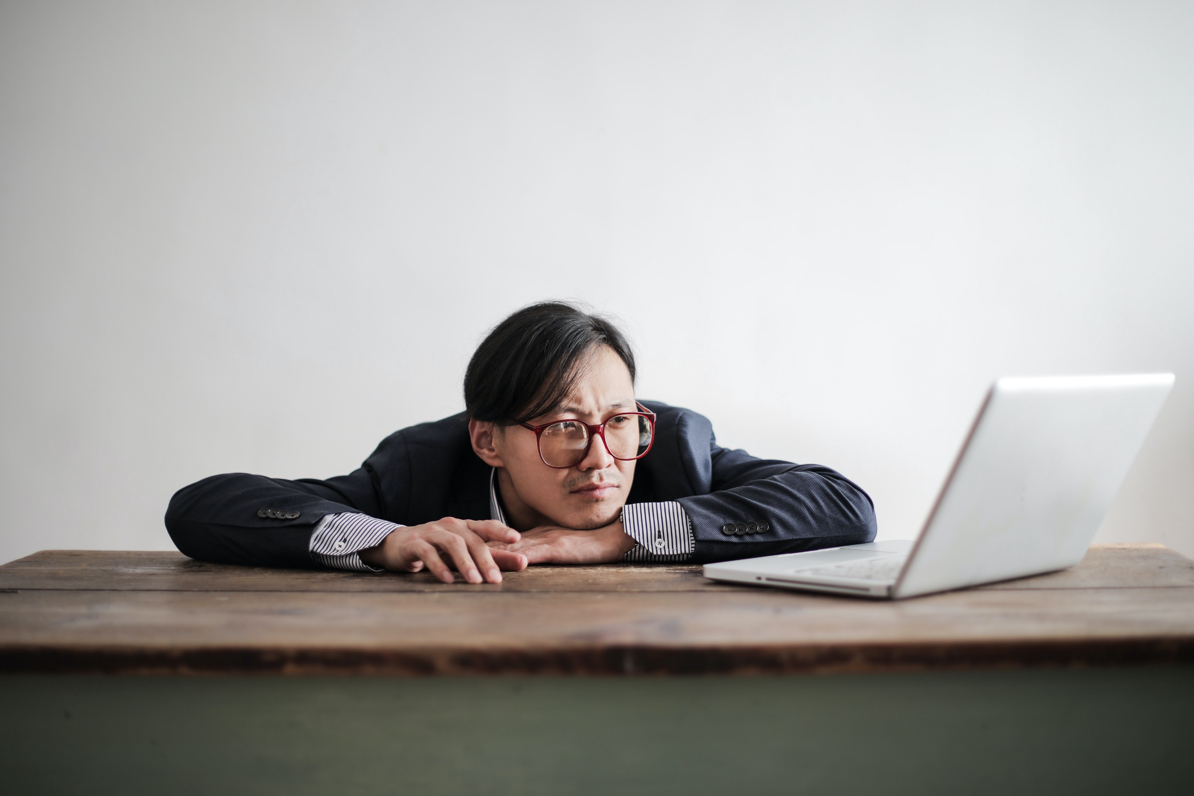 A man dressed in a blue suit wearing red glasses with his chin on his wrists, staring defeatedly at an open laptop.