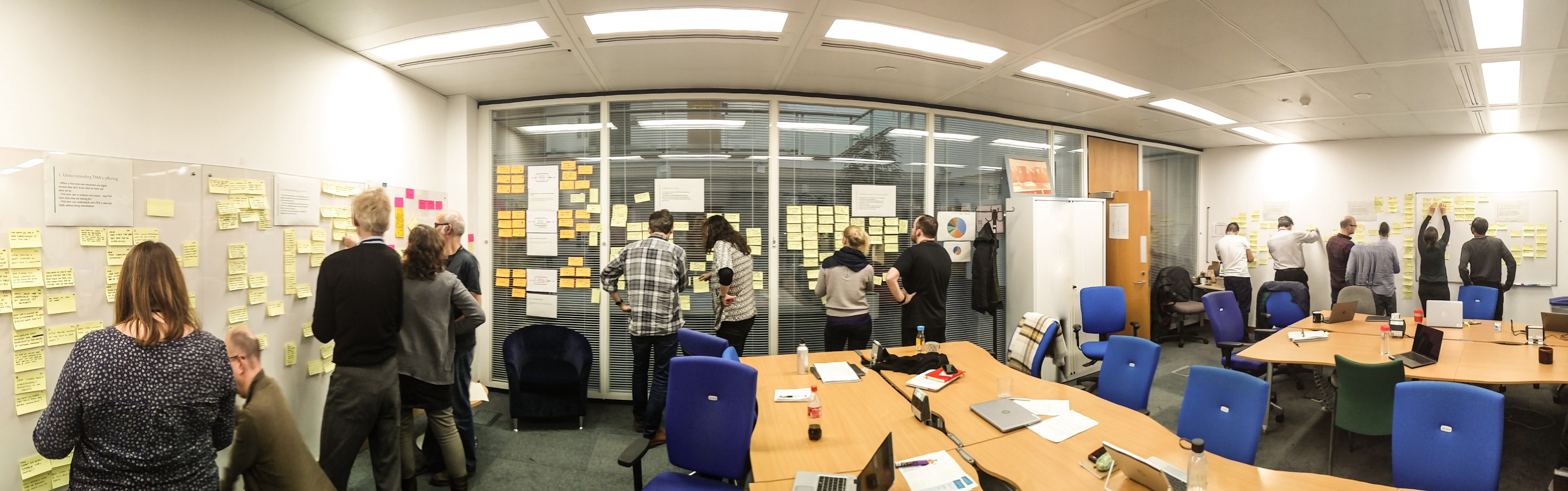 Team members working in pairs and clustering how might we statements written on sticky notes