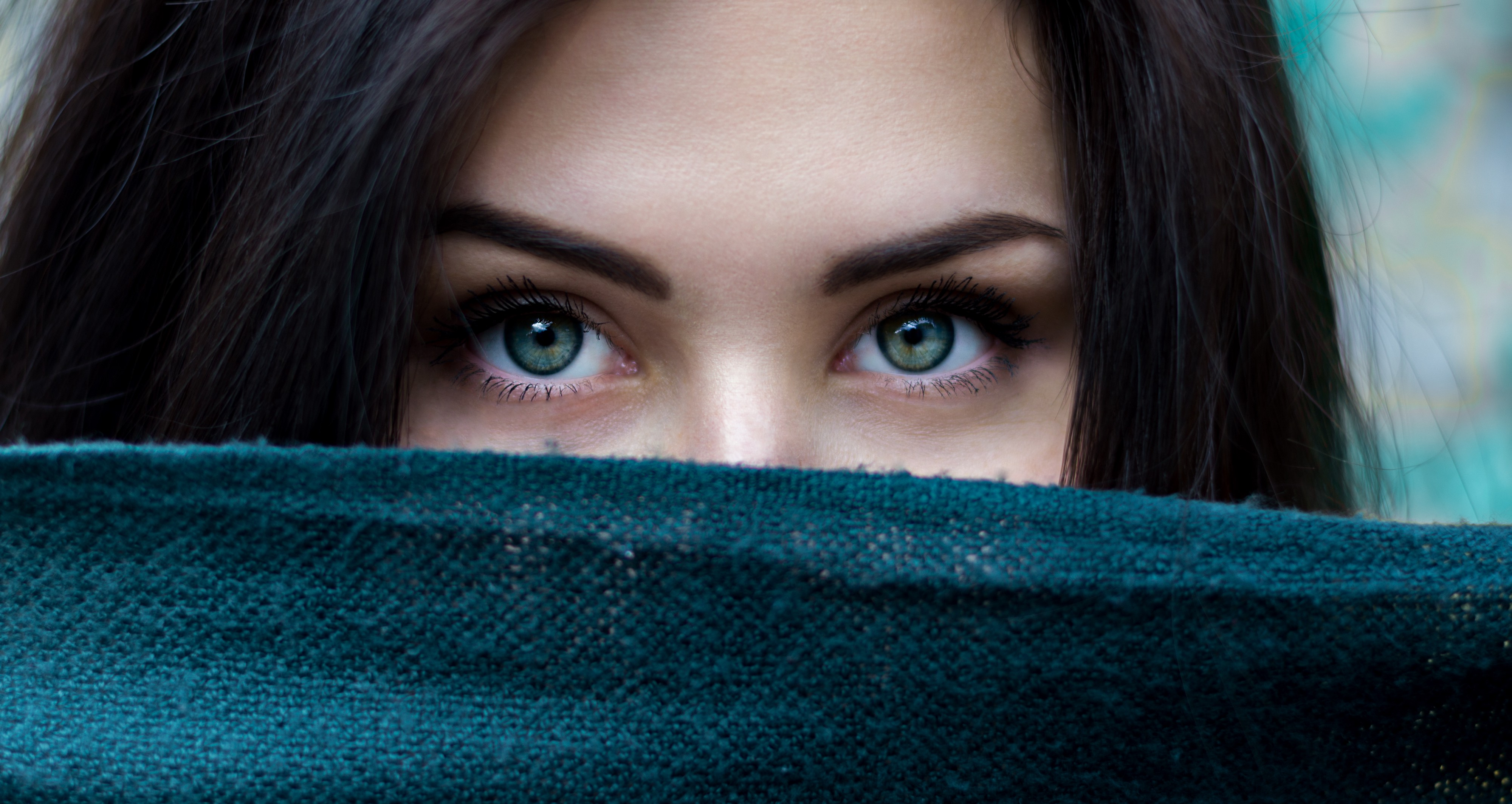 A young woman with green eyes, hiding behind a blue blanket, so you are unable to see her entire face.