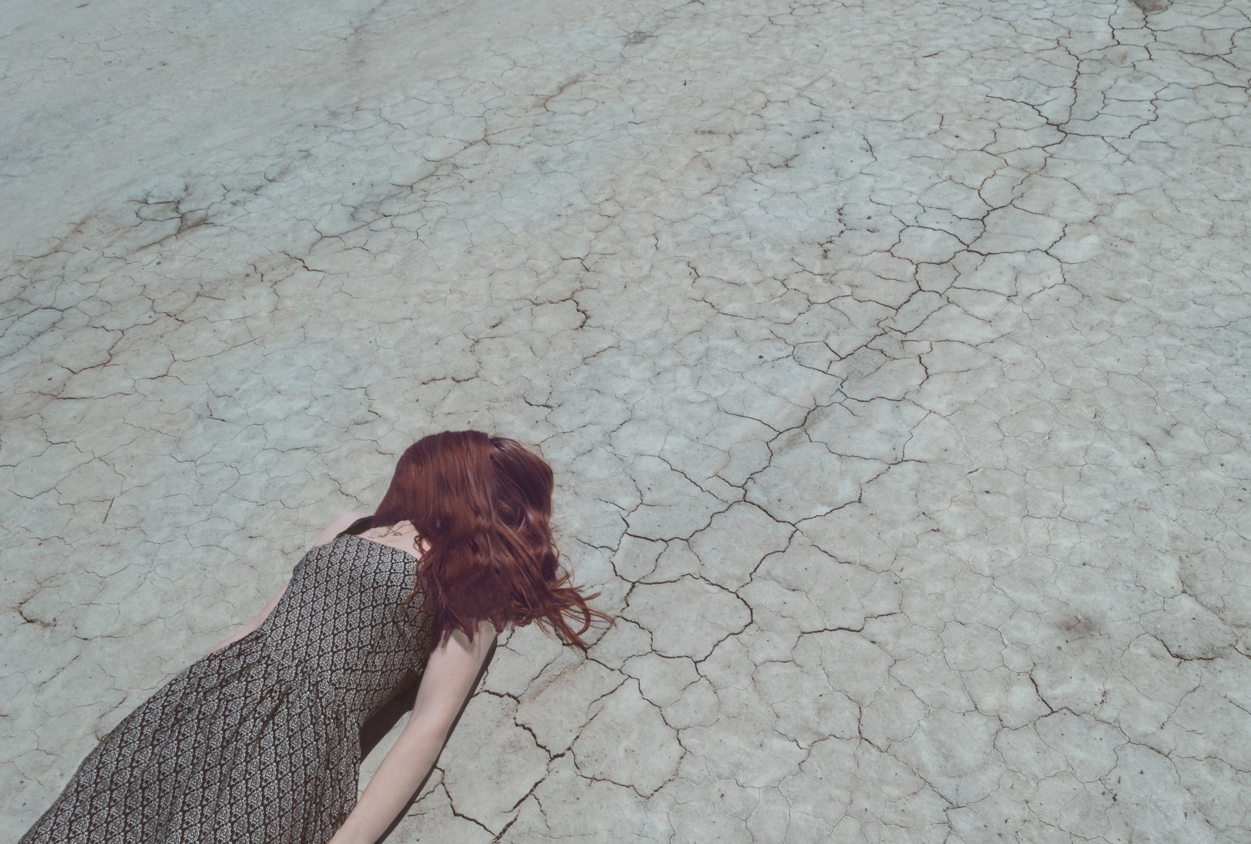 Girl with hair over face lays on drought landscape