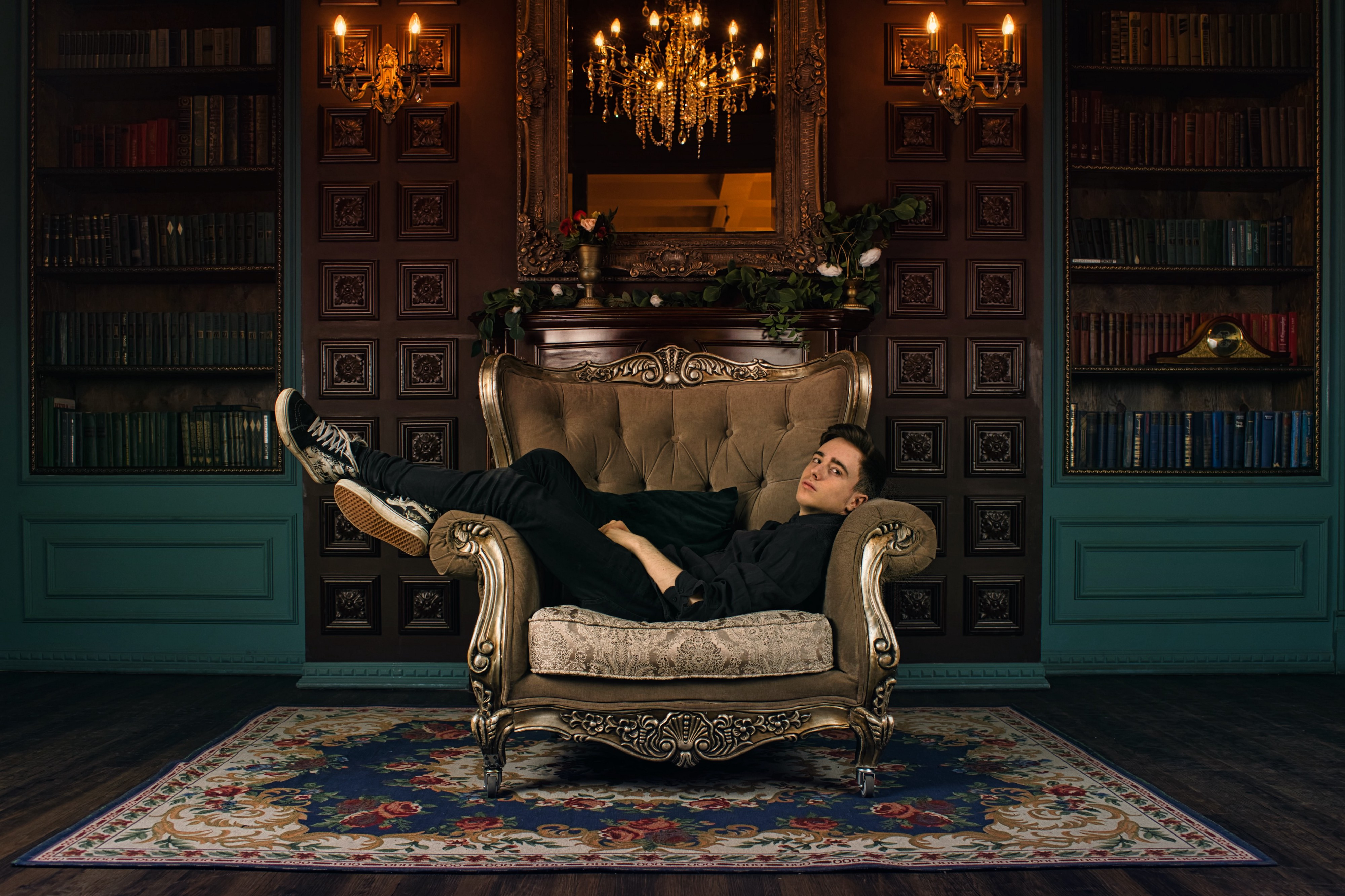 A casually dressed man laying across an expensive sofa