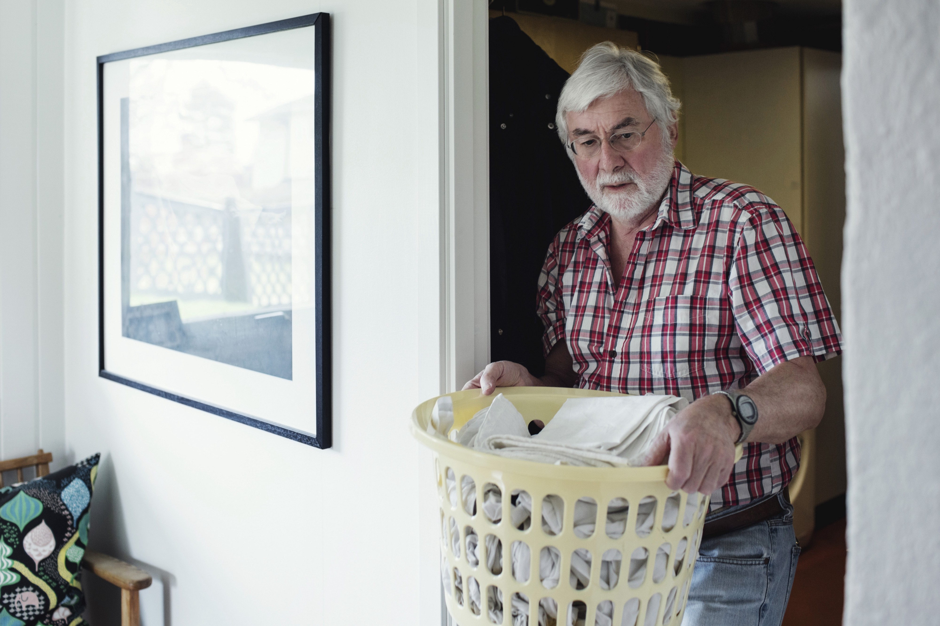 A man holding laundry basket while walking through doorway at home