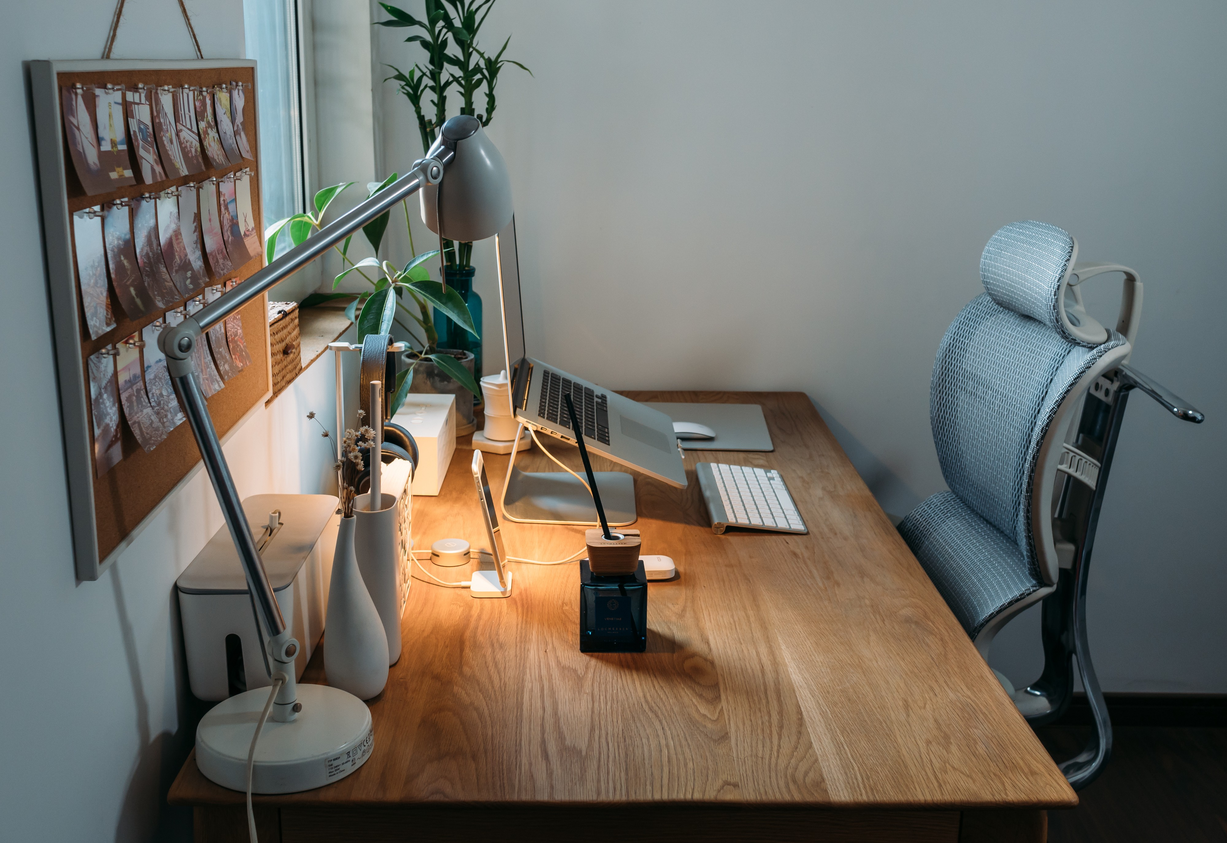 Work from home setup with wooden desk, sat directly at a small window, with minimal appliances, several small plants, a macbook on a standard, a keyboard and a mouse. On the wall there is a cork board with pinned images into it.