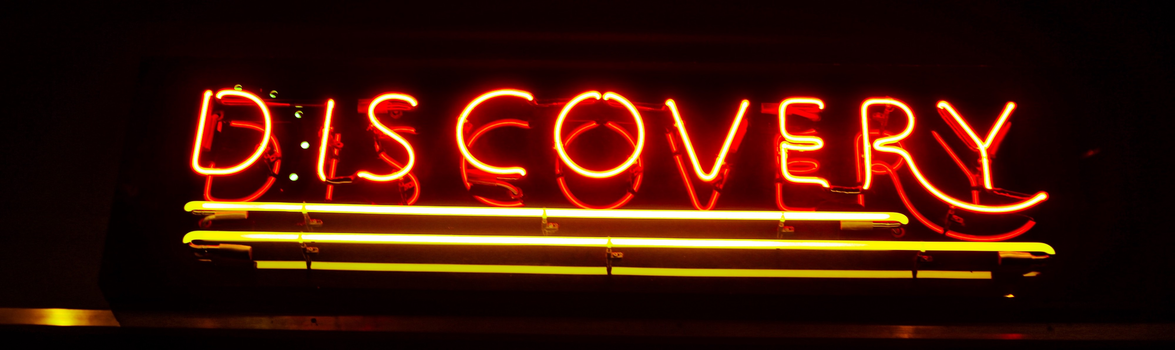 """A photo of a neon sign that reads: """"Discovery"""""""