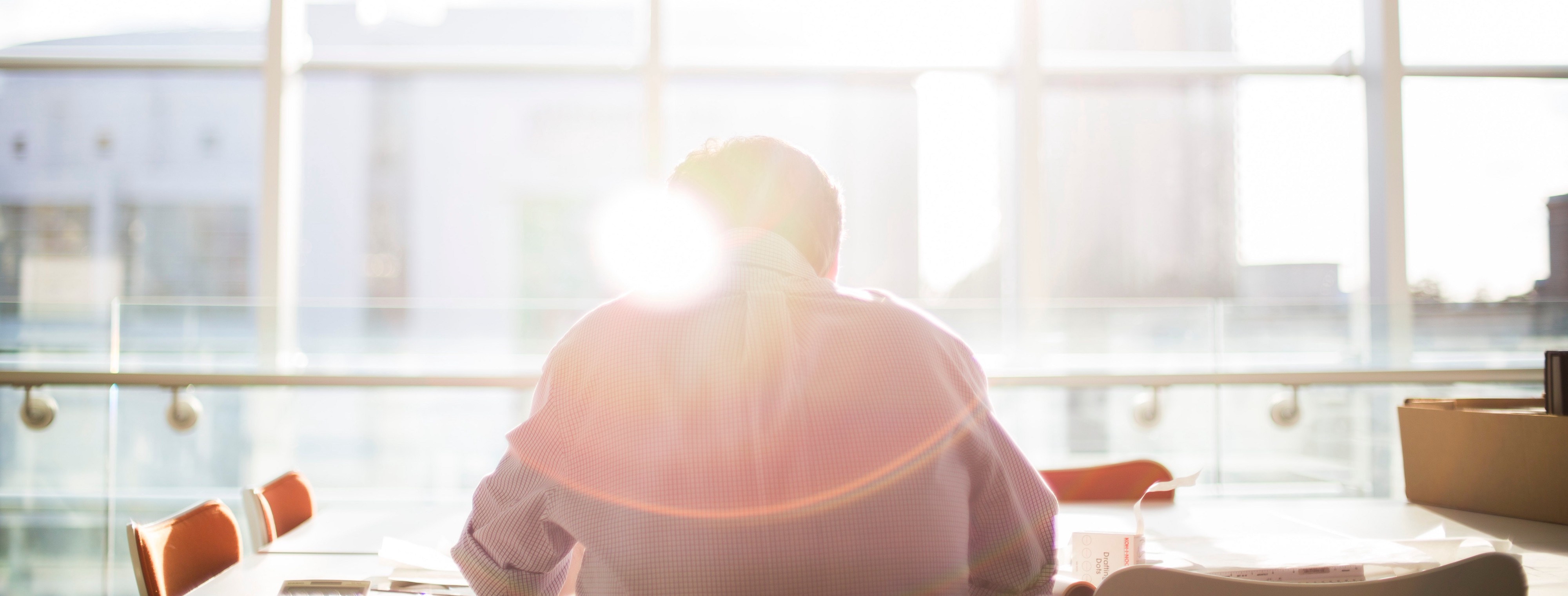back of a man sitting on an empty conference room table with big window sunlight shining through