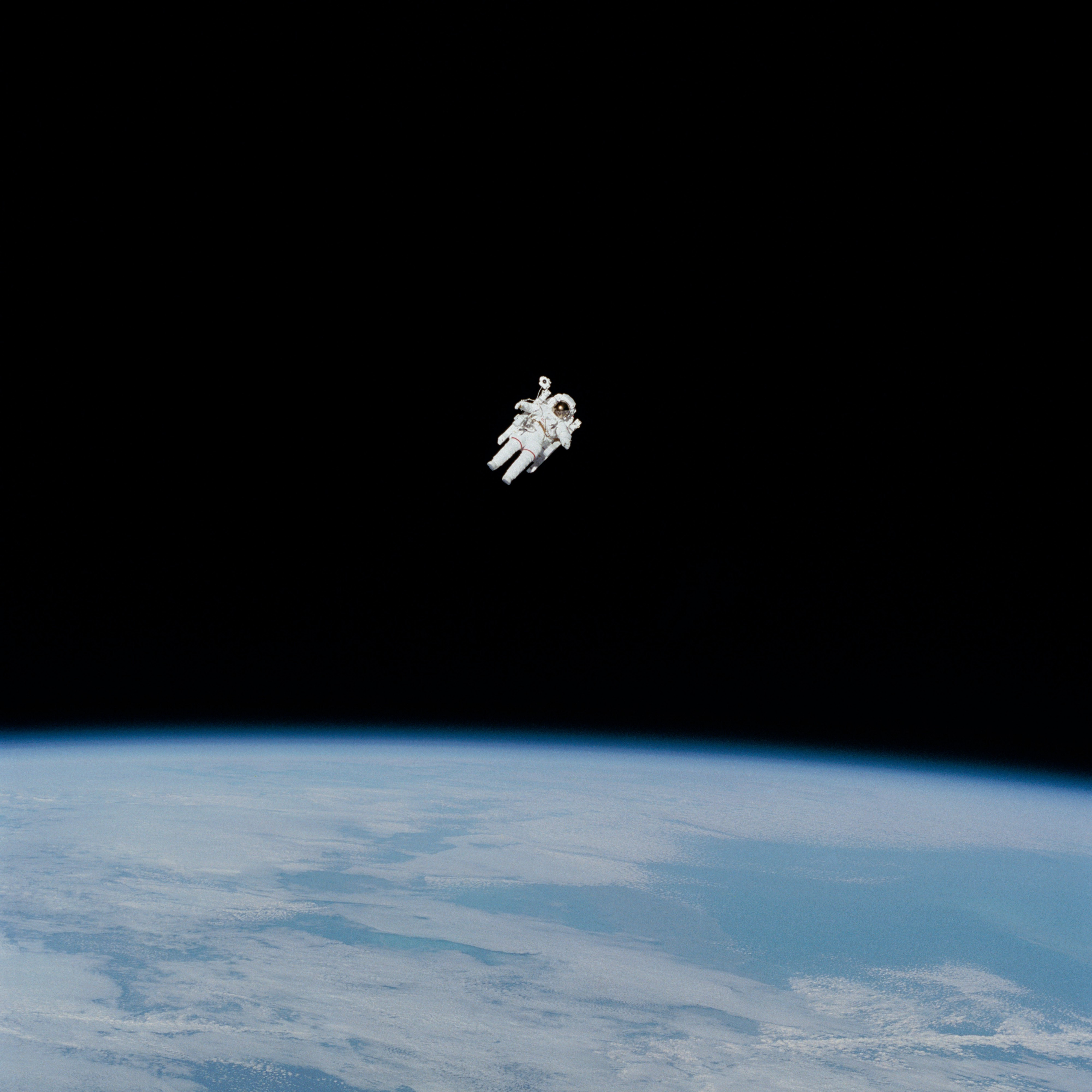 Astronaut floating in space, a minuscule white figure in the vastness of the cosmos