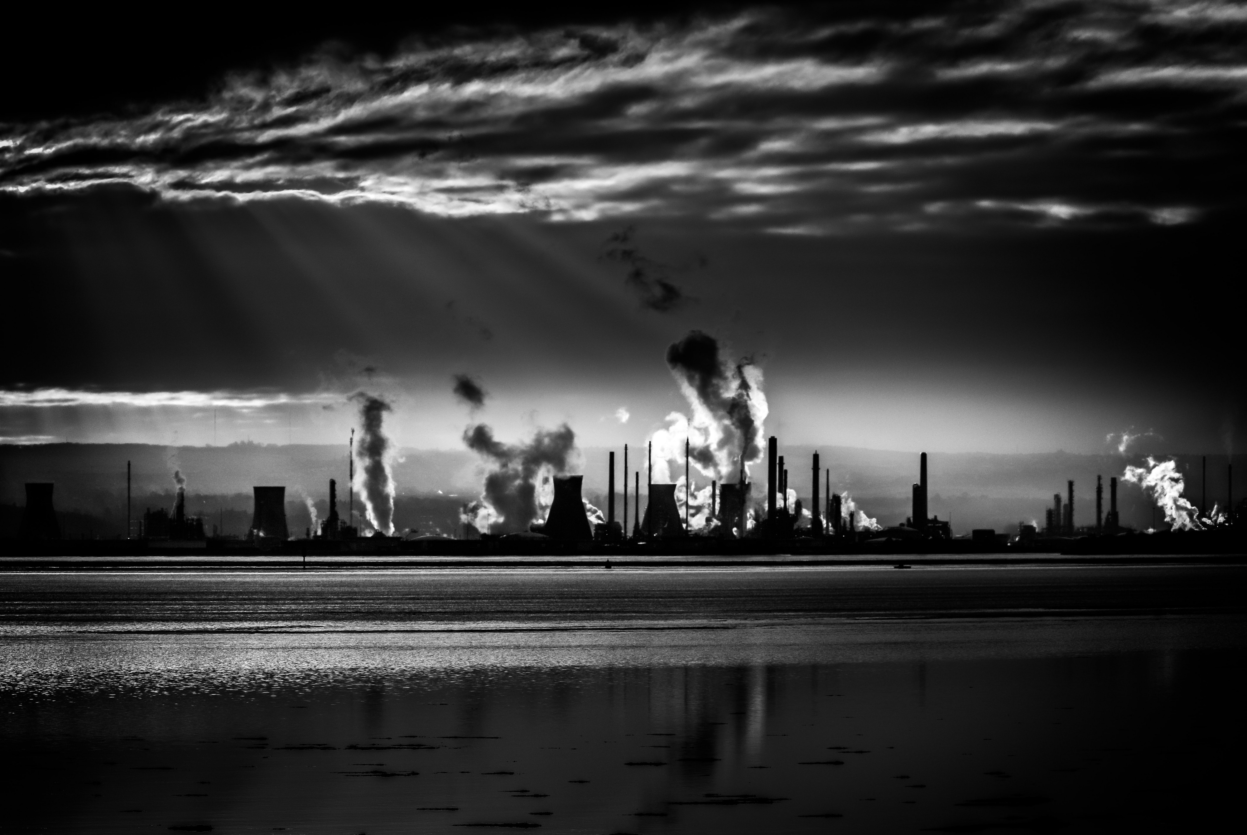 Silhouette of a power plant with cooling towers and trails of clouds.