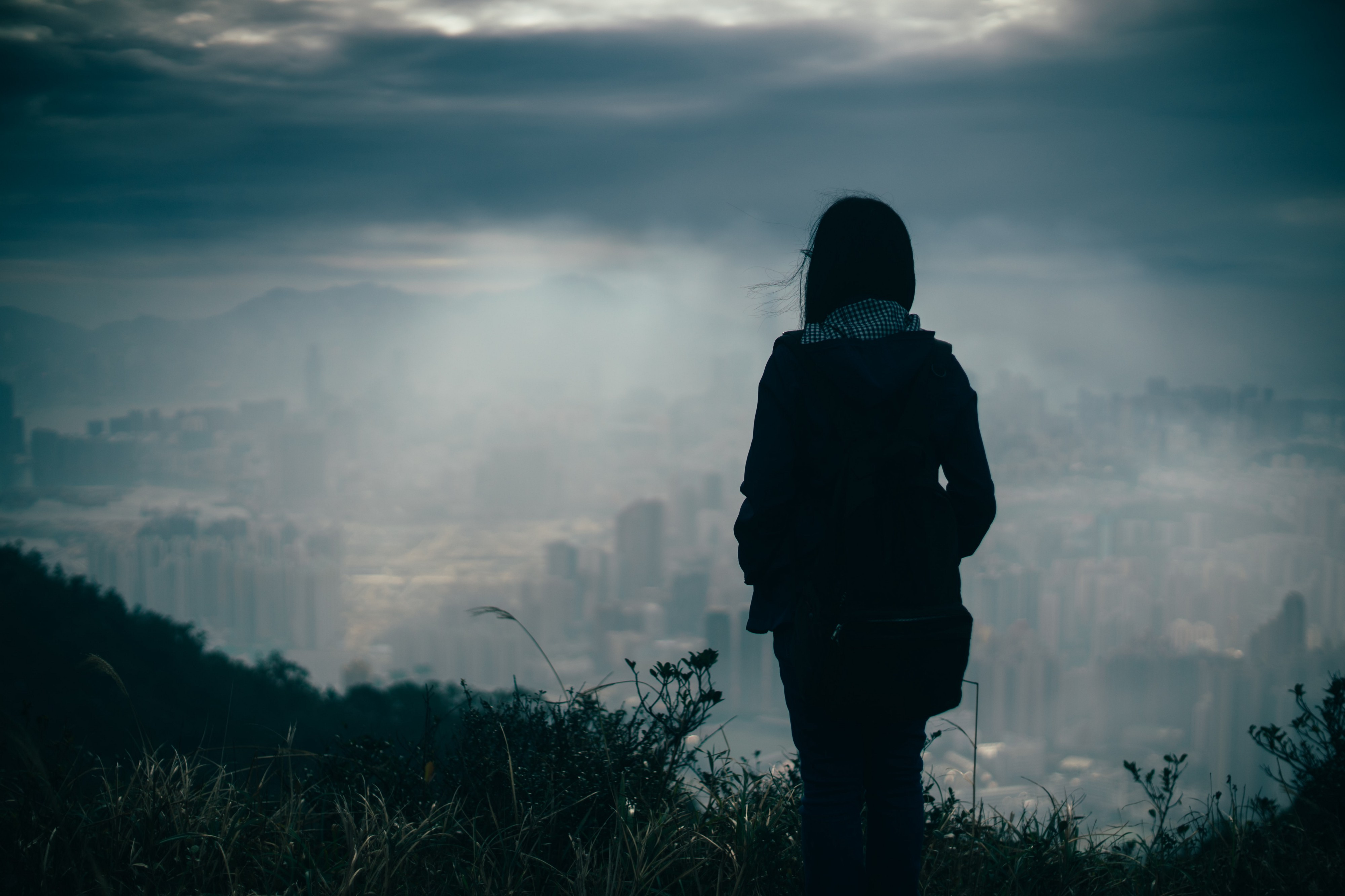 woman looking out over dark city scene with clouds in the sky