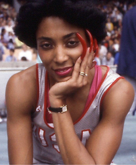 Florence Flo Jo Griffith-Joyner stares at the camera, smiling and showing off her colorful long, red nails. She has an Afro