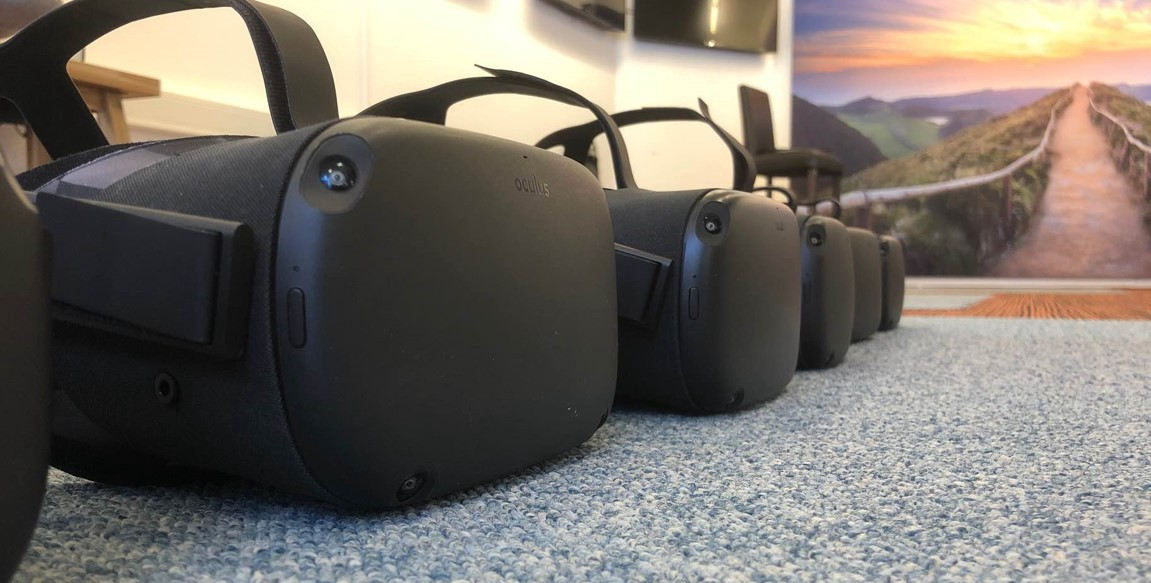5 VR headsets lined up on the floor