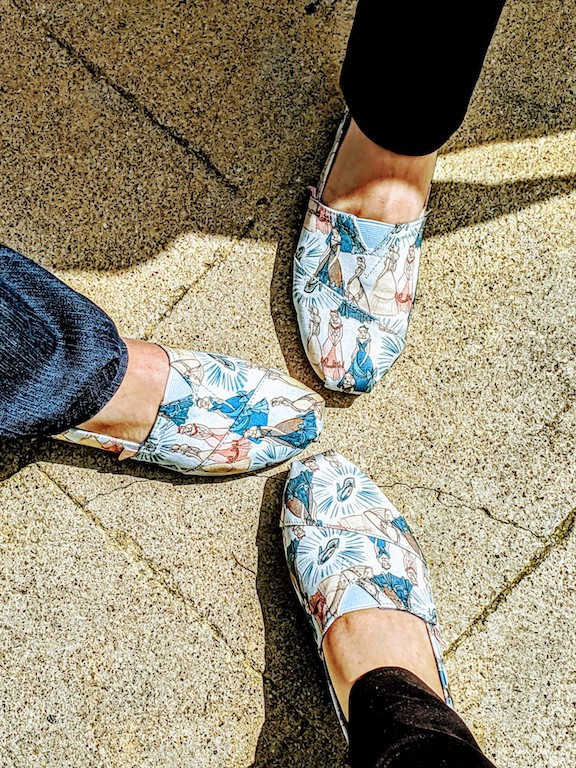 Three feet, wearing the same shoes with a Disney Princesses pattern