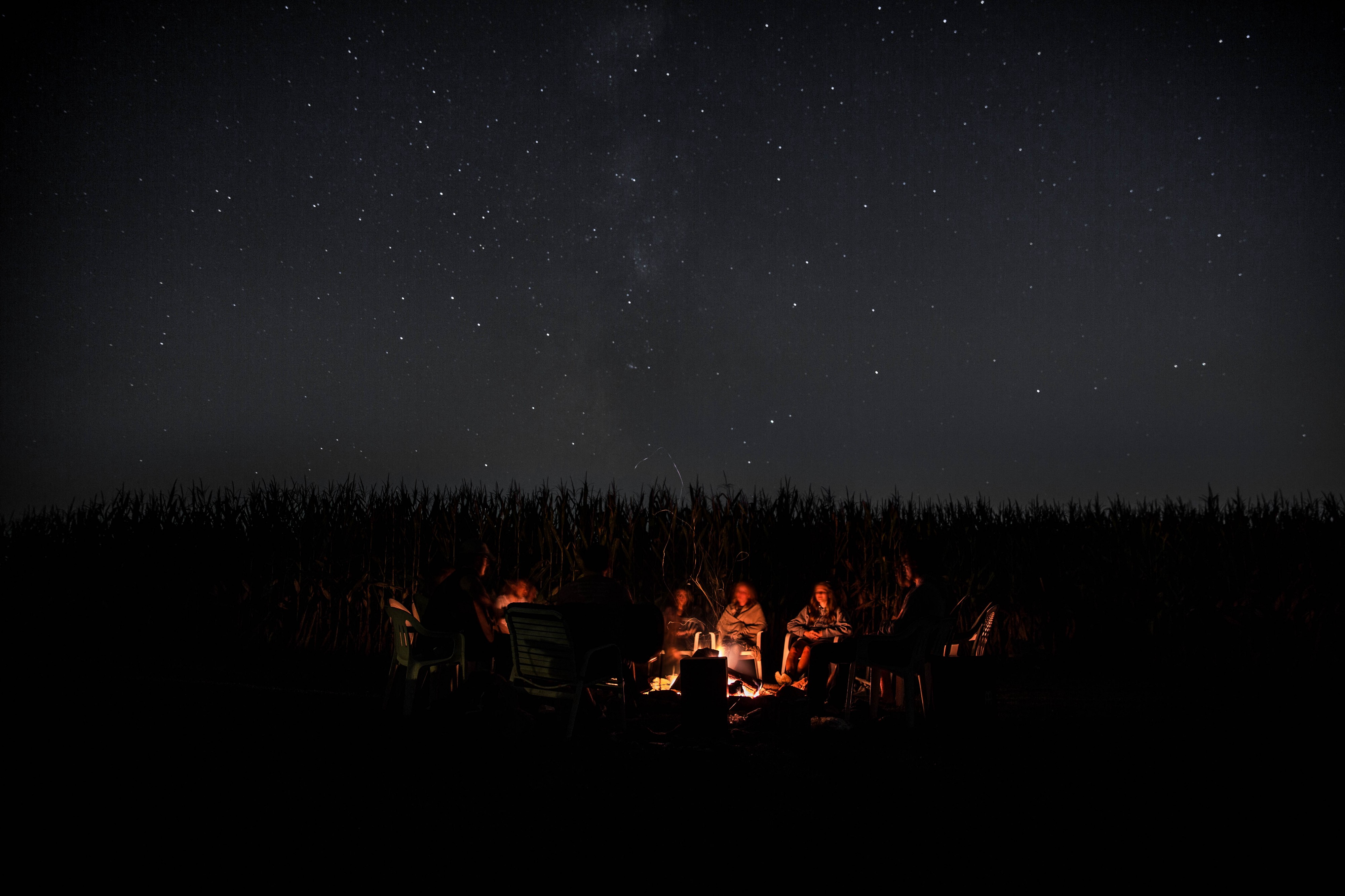A group of people sitting around a campfire underneath the stars.