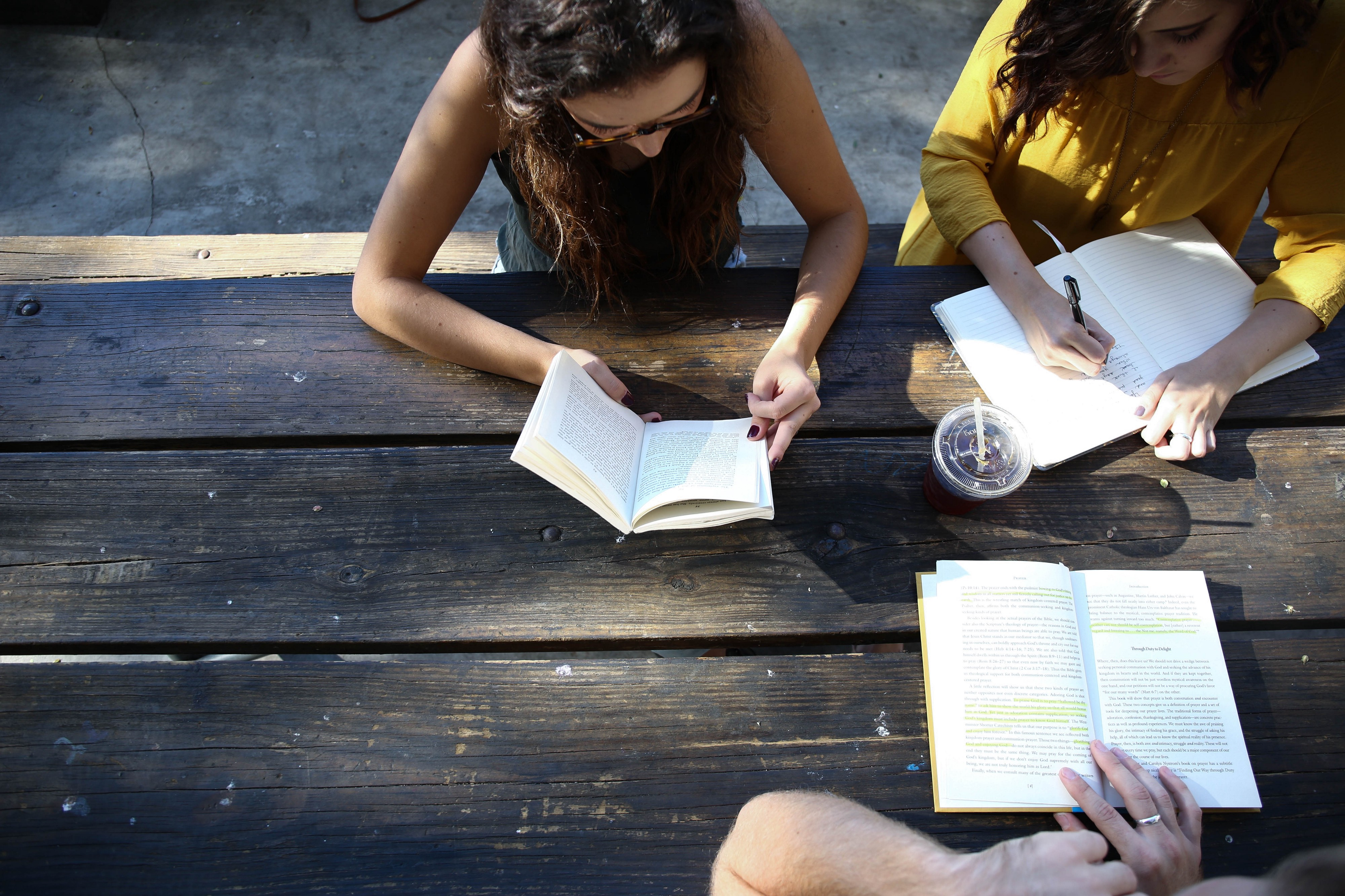 Three students studying at a picnic table outside.