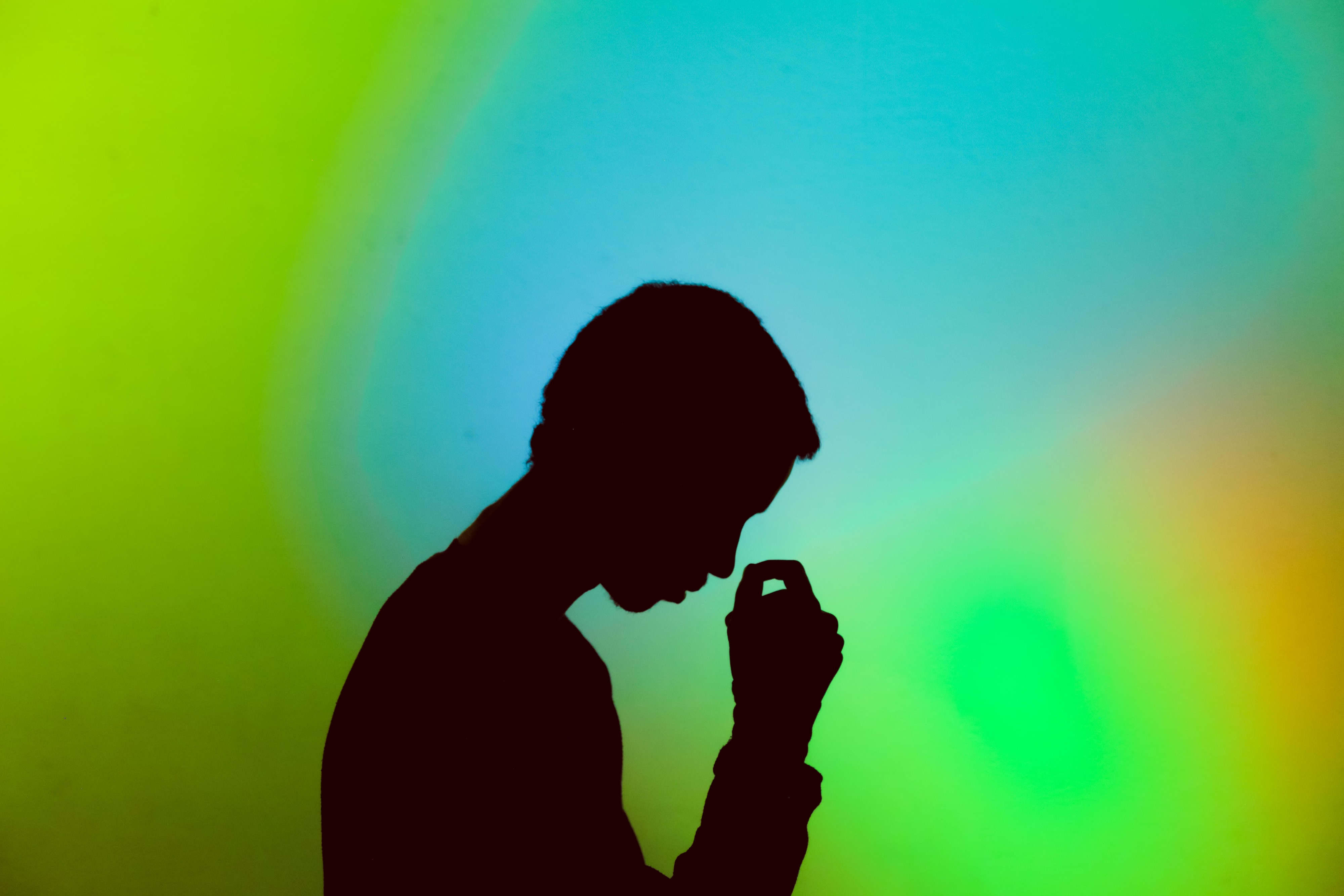 A silhouette of a man looking sad and holding his head down.
