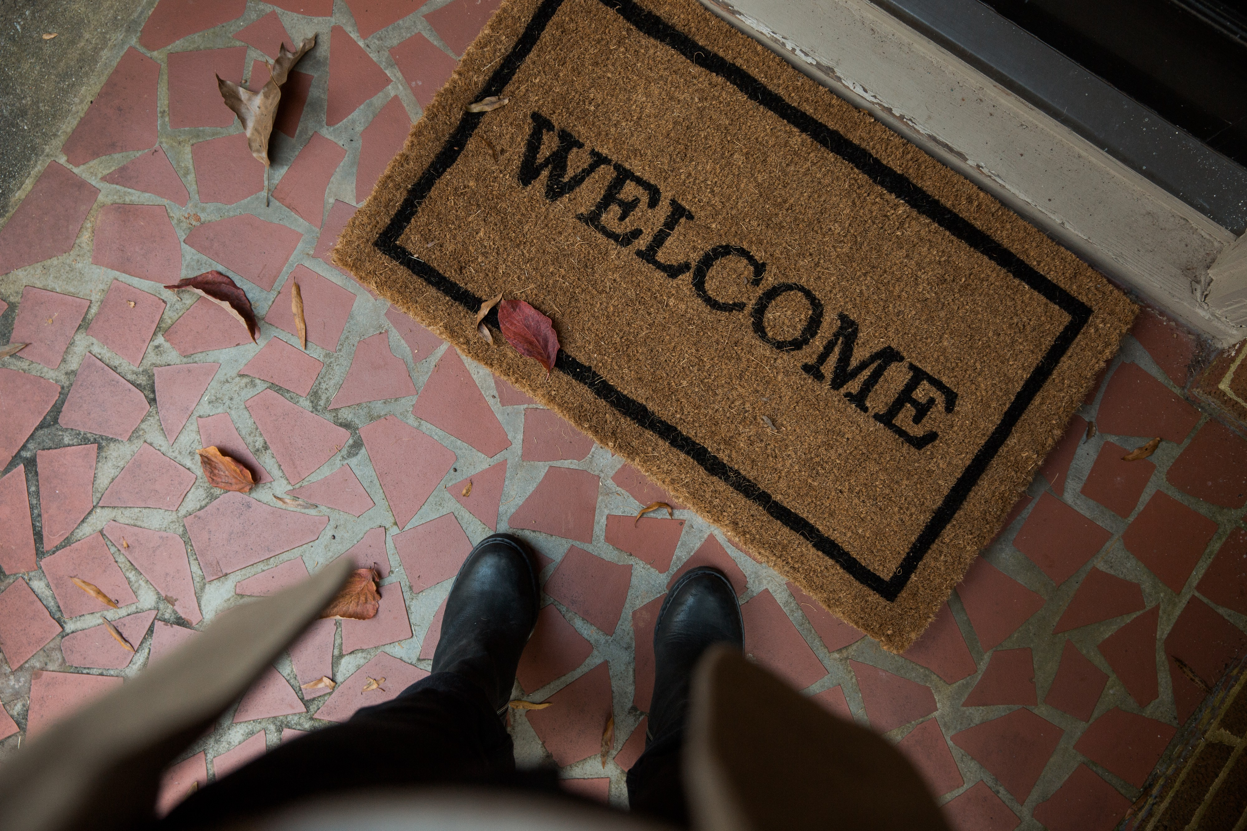 Person standing in front of welcome mat that says 'welcome'