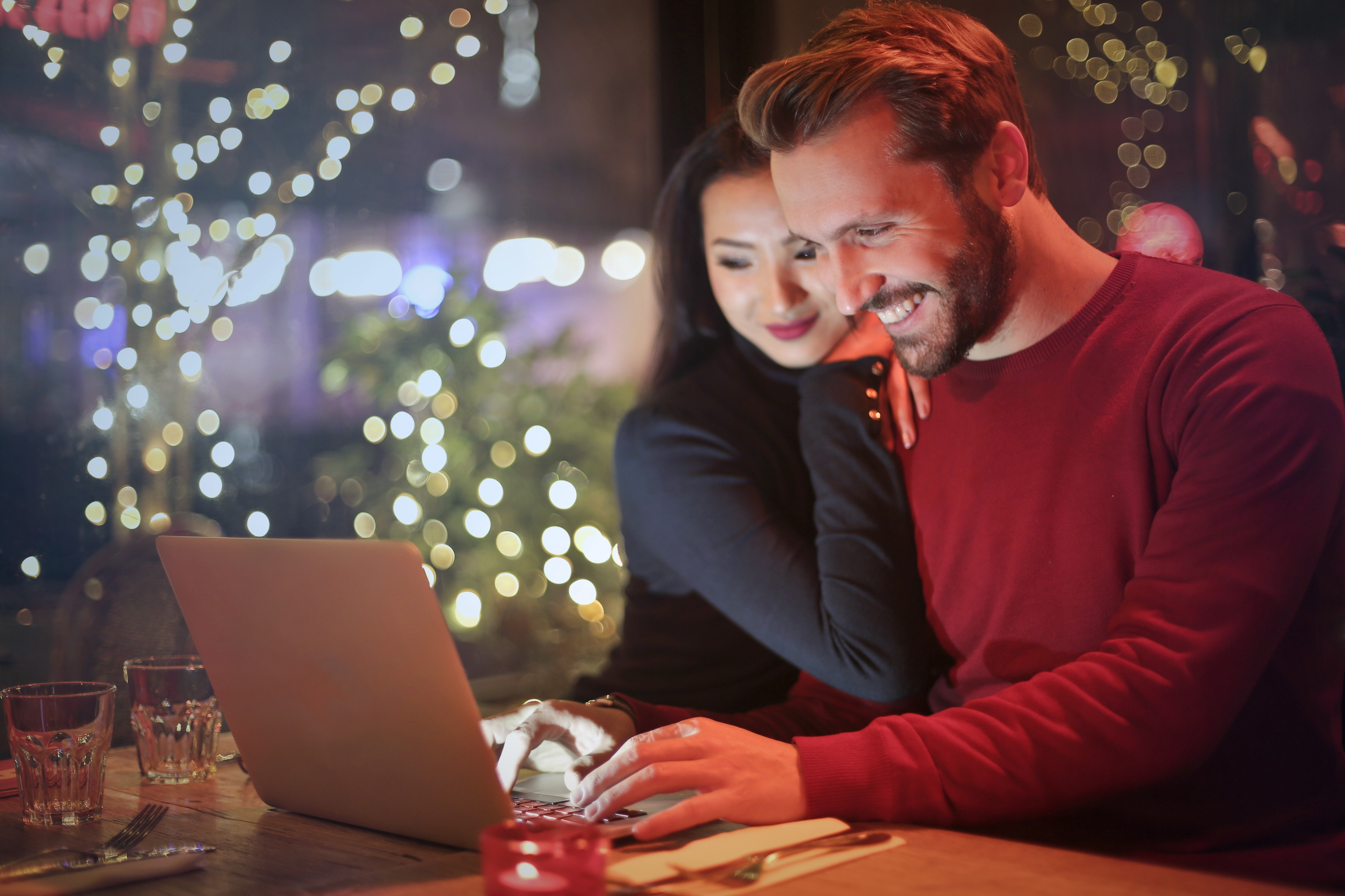 Interracial couple at a restaurant with laptop opened. The woman leans on man's shoulder. Fairy lights in the distance.