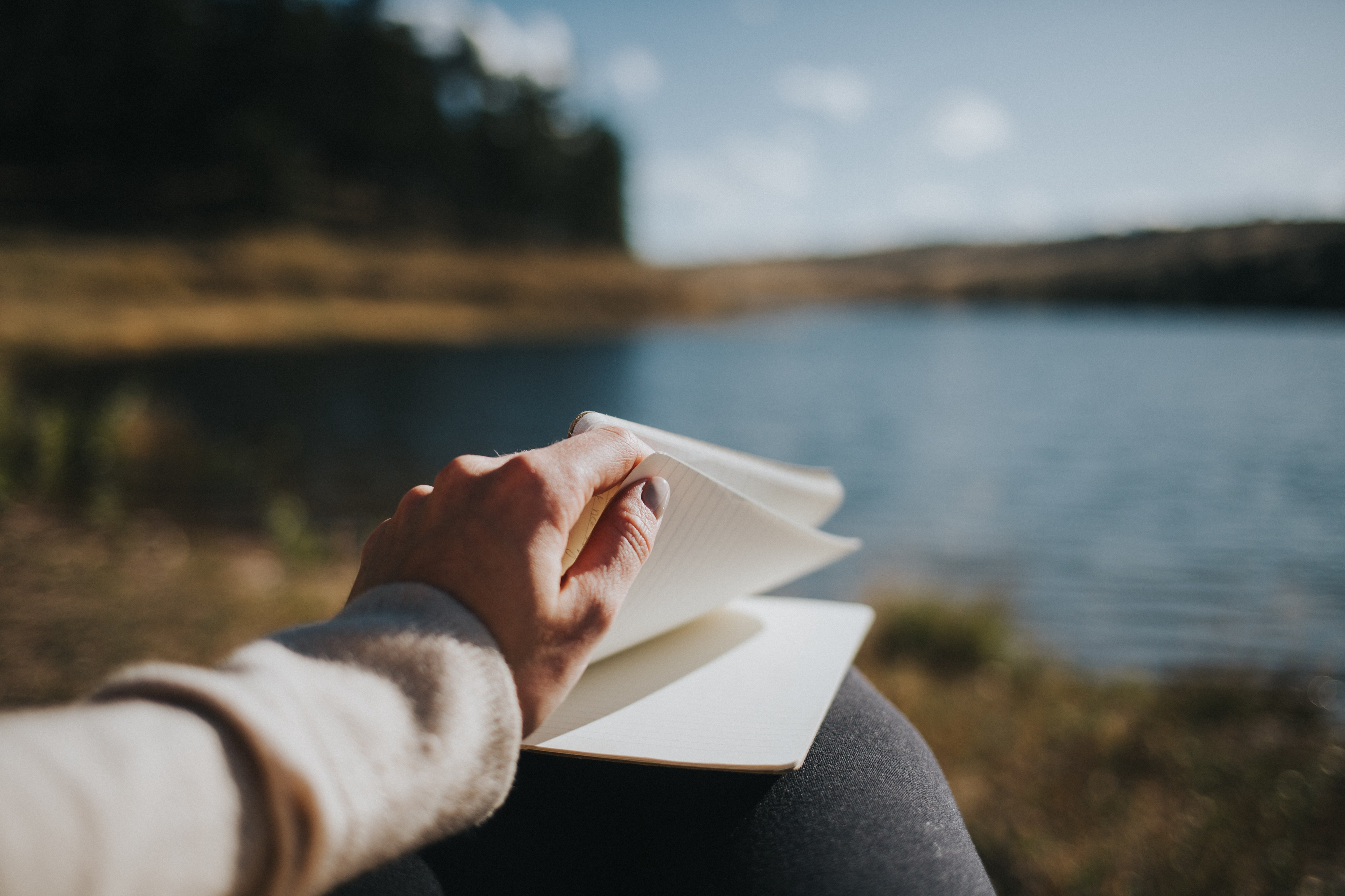someone leafing through a journal beside a lake