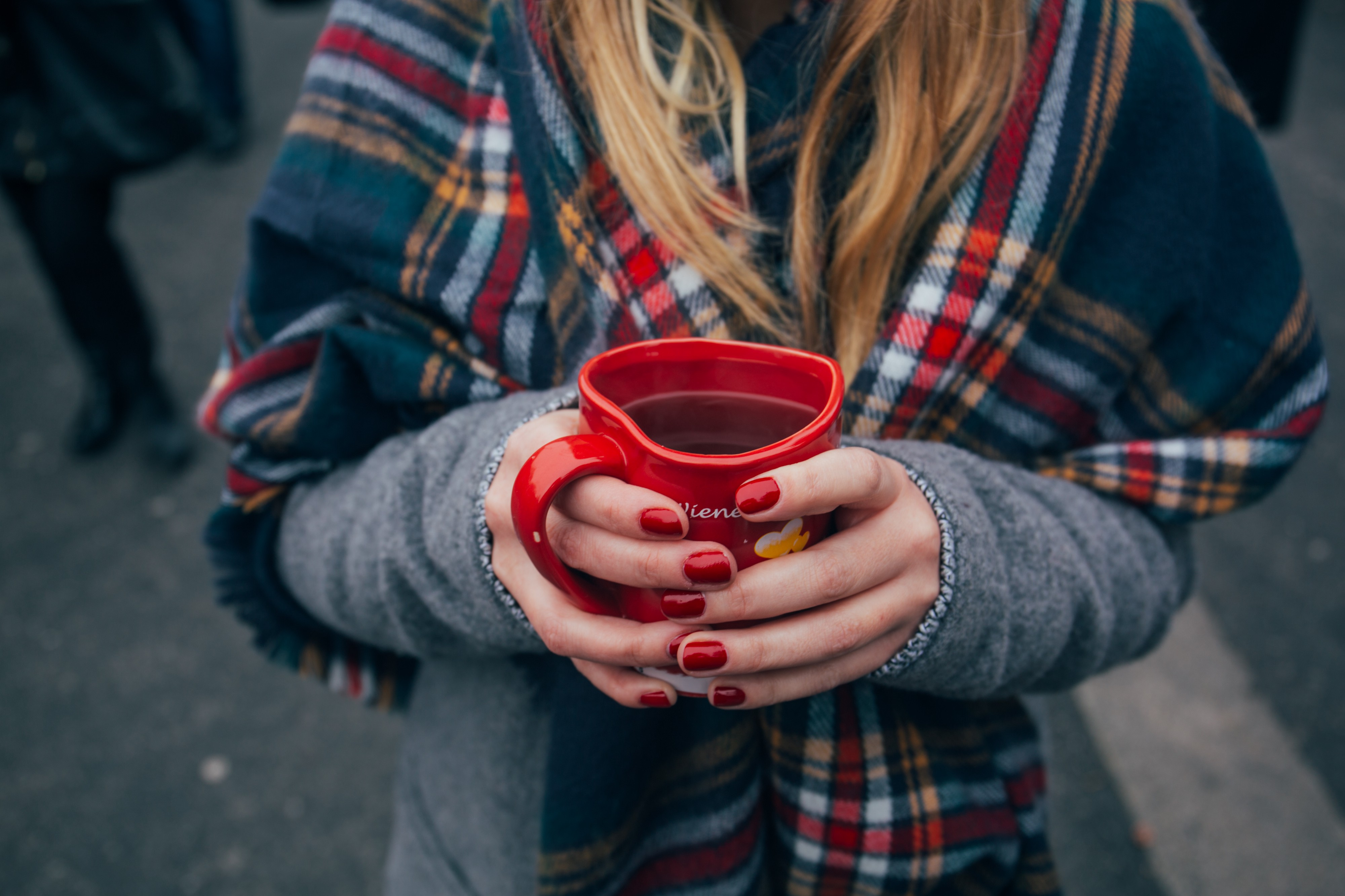 Woman with red-painted fingernails, holding a red coffee mug
