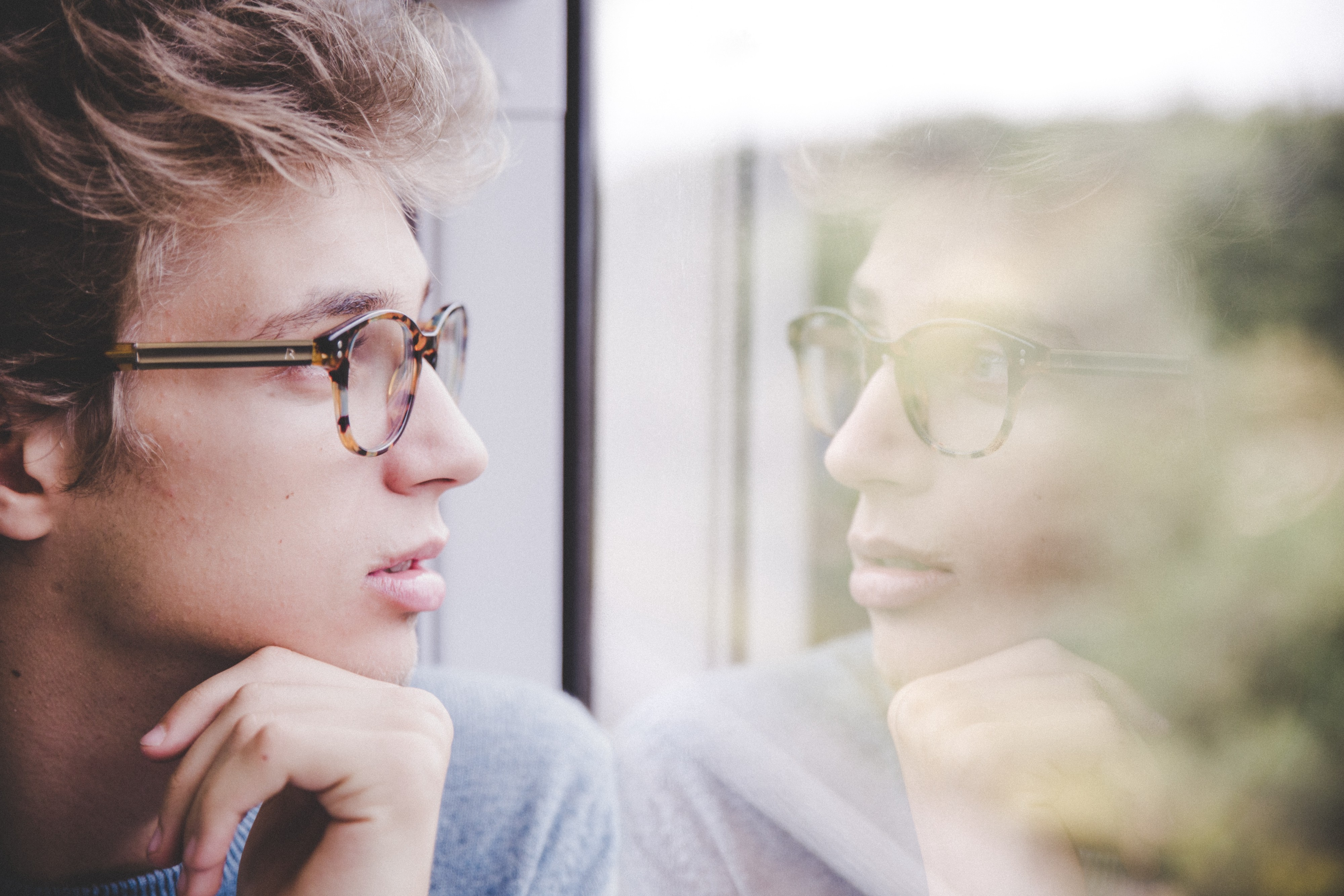 Young man with glasses looking contemplativly at his reflection.