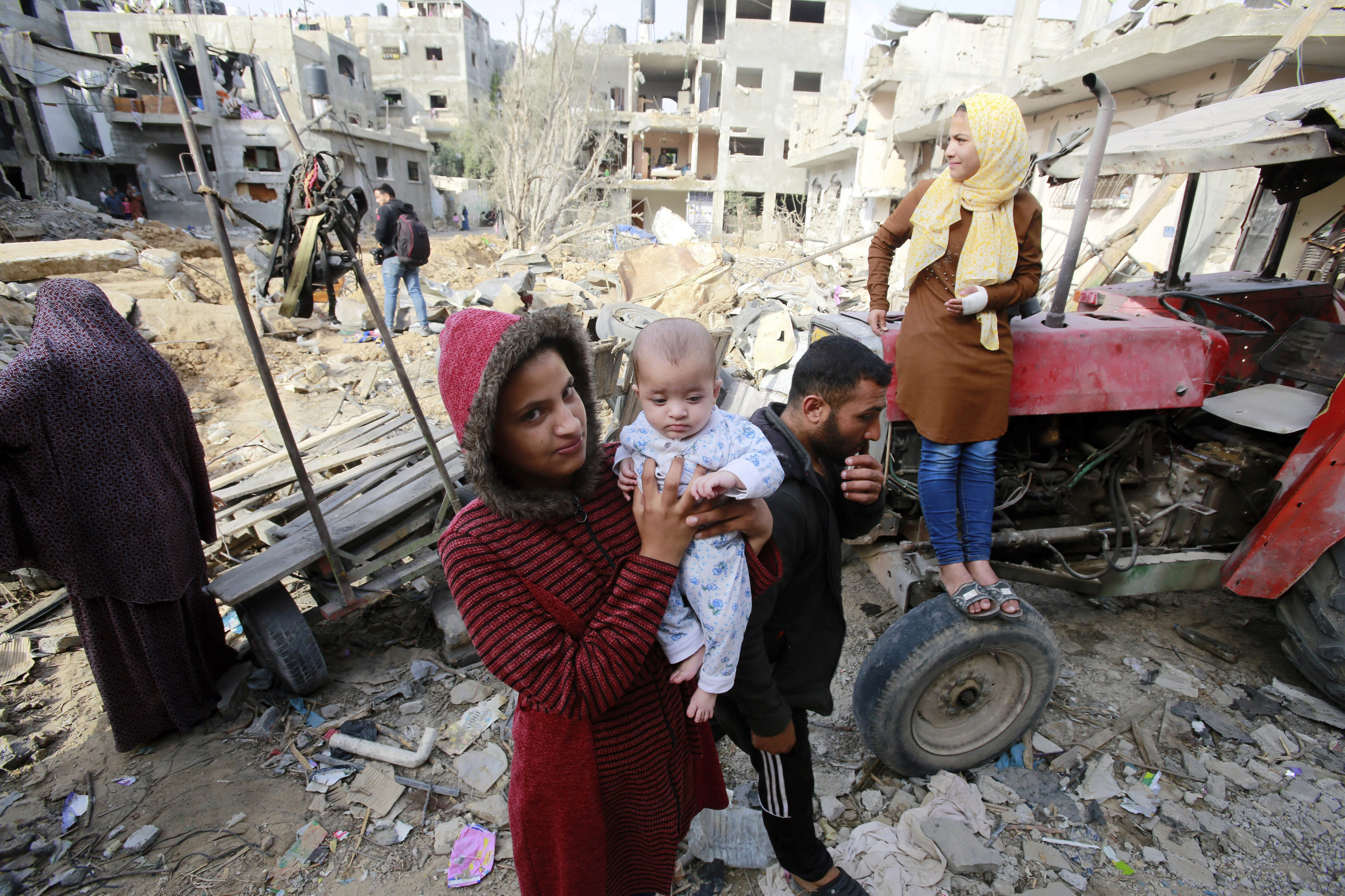 Palestinian family who have returned to their neighborhood, stare at the damages from their home, hit by Israeli bombardment in Gaza City—21 May 2021. (Photo by Ahmed Zakot / SOPA Images/Sipa USA)(Sipa via AP Images).