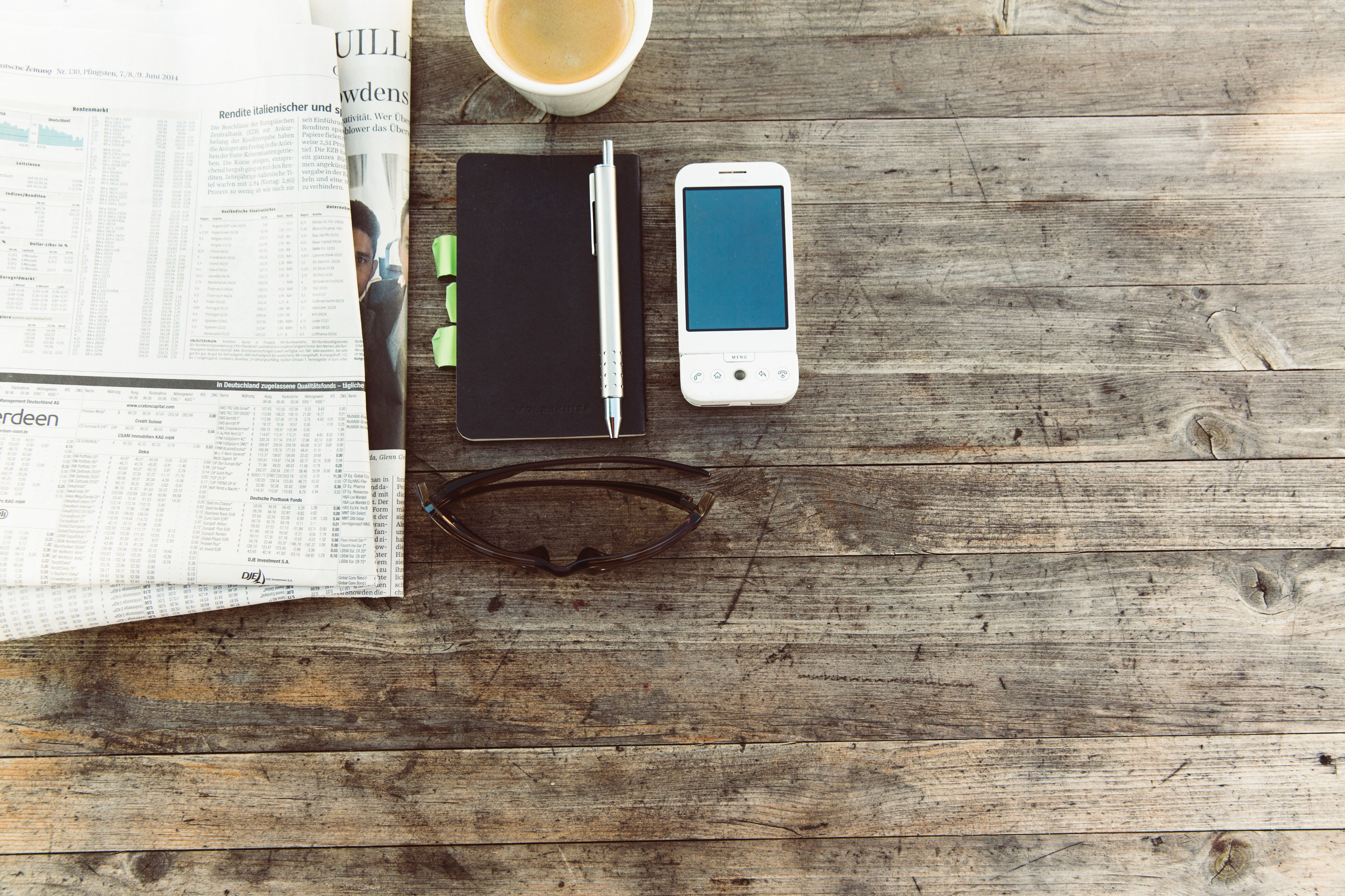 a phone and newspaper sitting on a wooden table