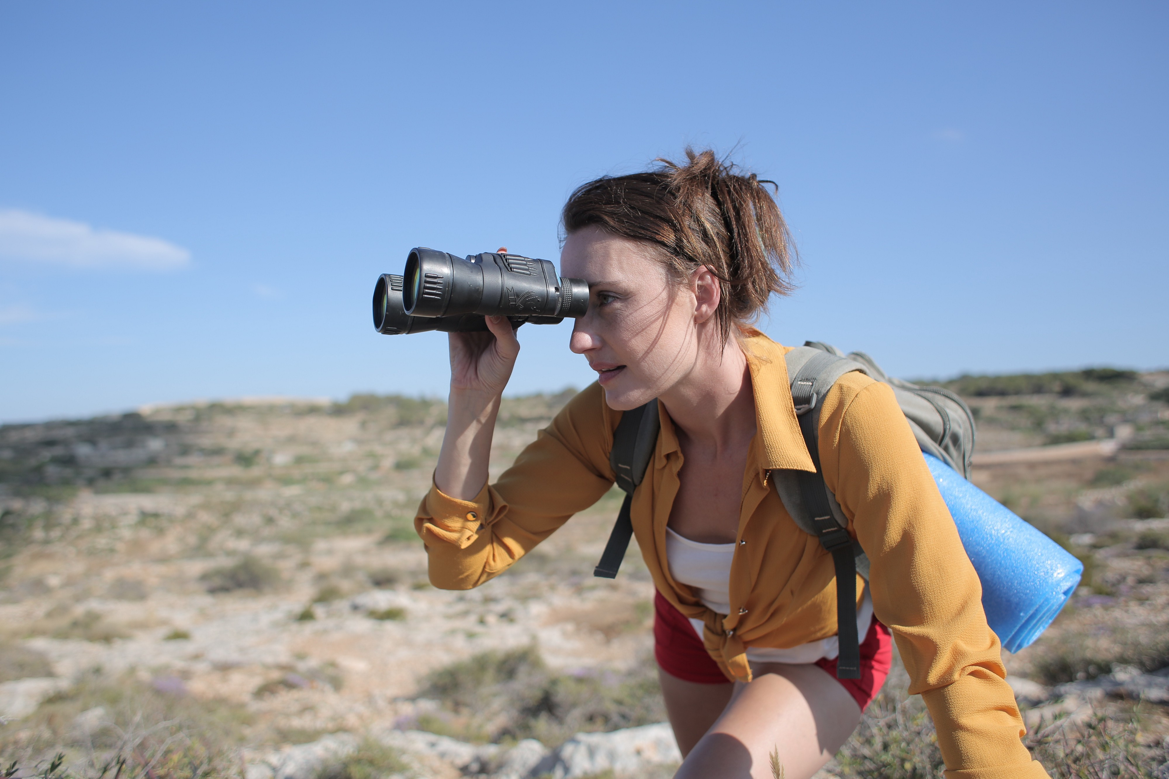 A woman in a yellow shirt and red shorts is outside, bent over and peering intently at something in the distance through a pair of binoculars.