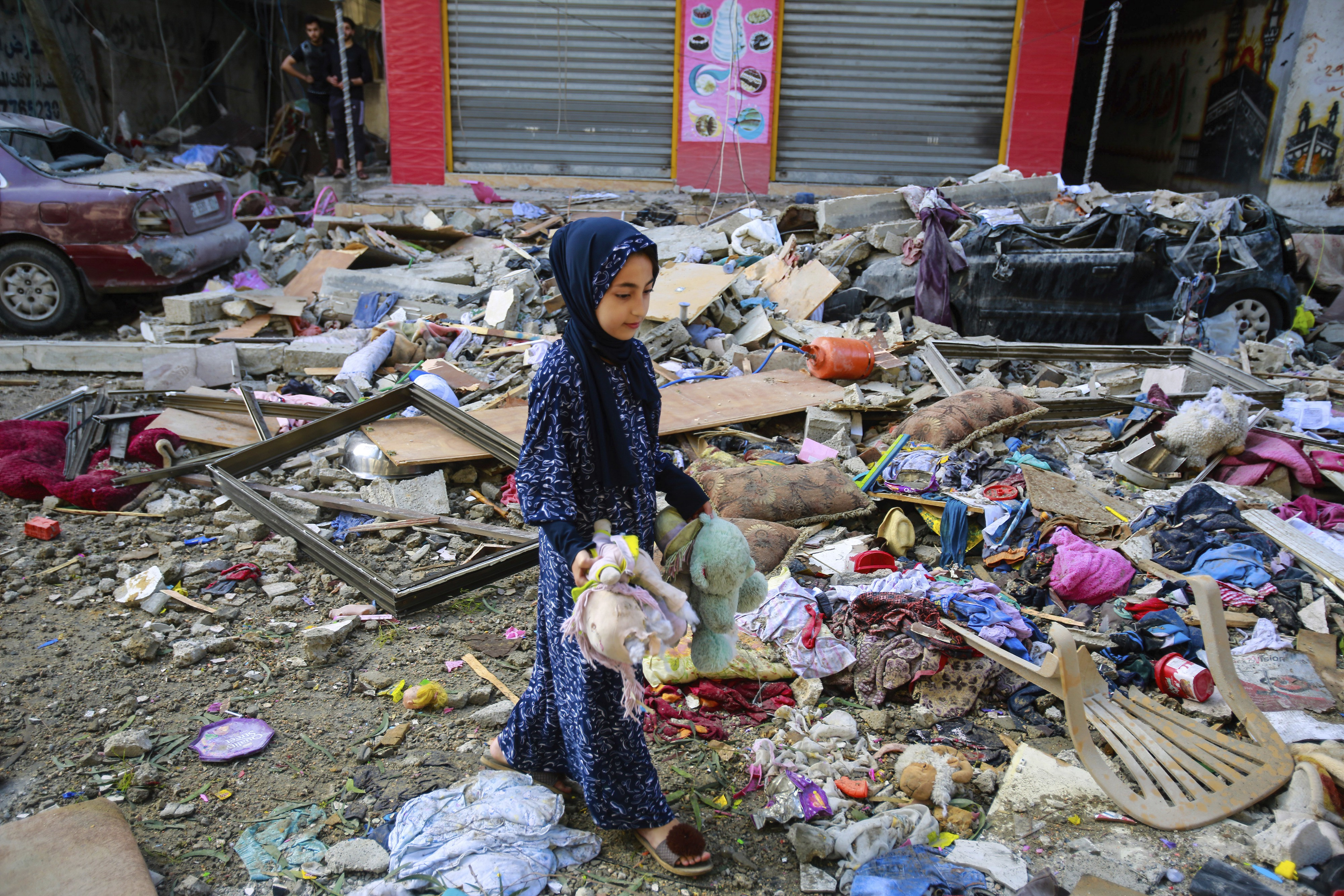 A Palestinian girl stands amongst destroyed building to collect her neighbours bears and toys in the aftermath of an Israeli airstrike on Gaza—19 May 2021. (Photo by Ahmed Zakot / SOPA Images/Sipa USA)(Sipa via AP Images).