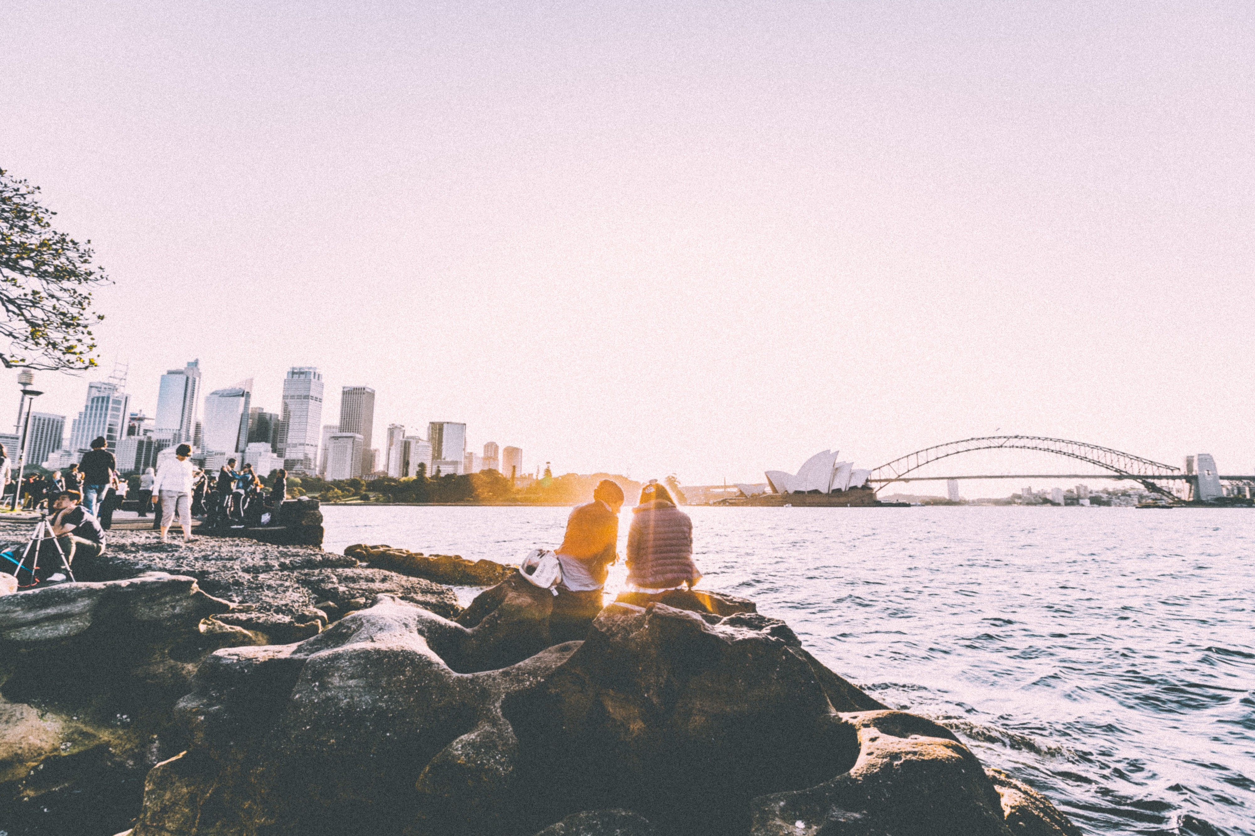 Coastal view of the Sydney Central Business District, the Opera House and the Harbor Bridge. People are seated on the rocks looking out at the harbor.