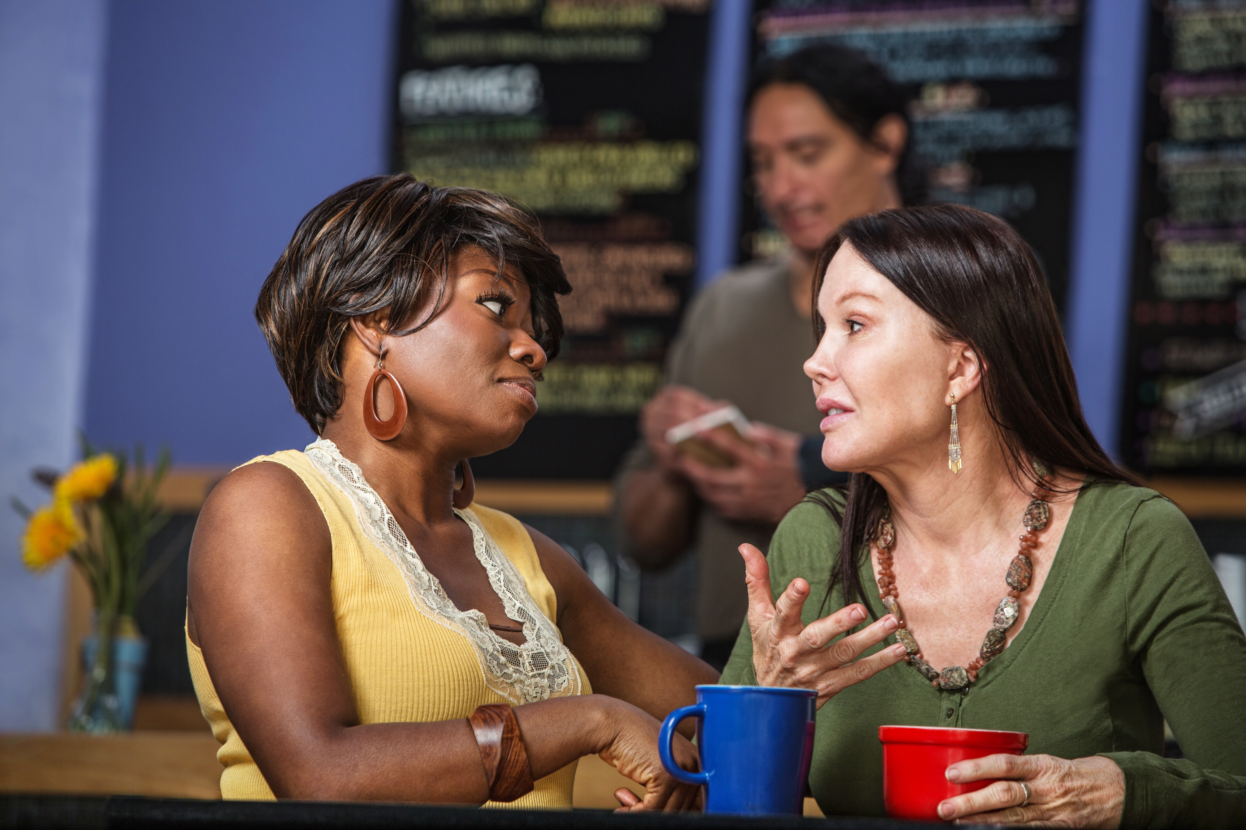 Two women (one clearly a person of color) conversing in a coffee shop