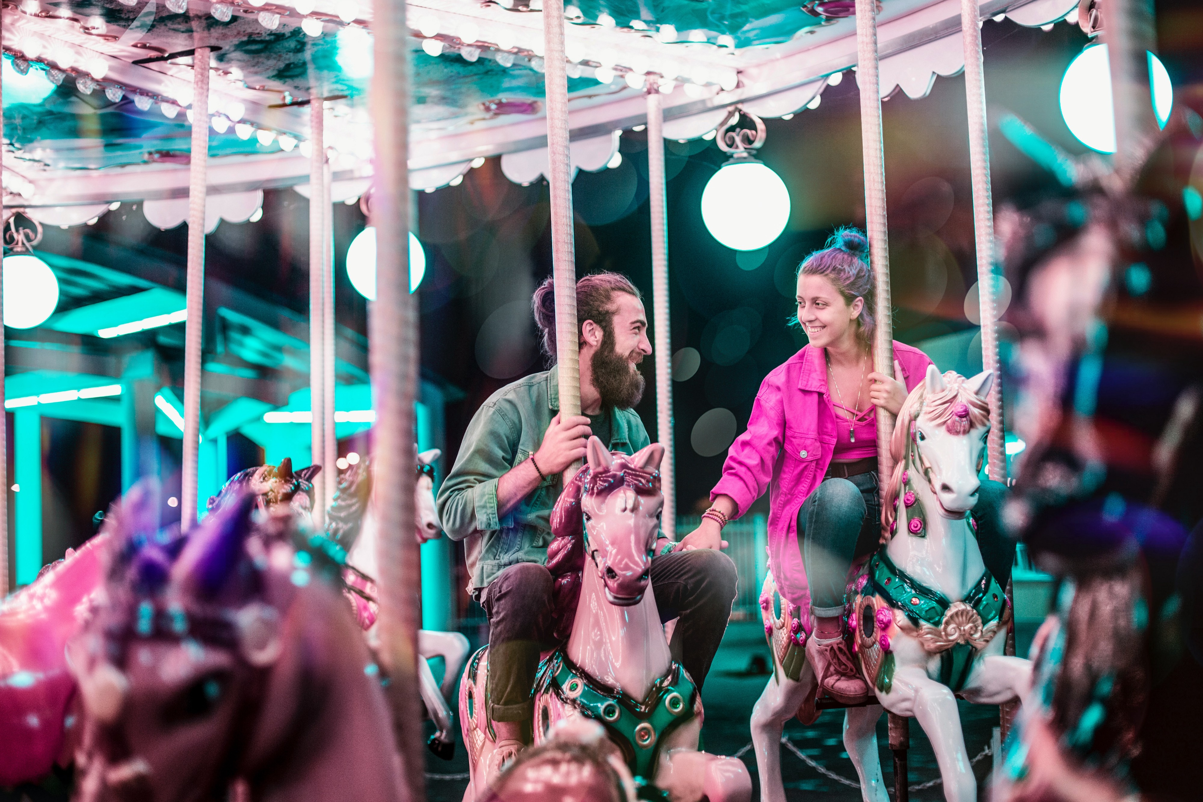 Two people riding a carousel and smiling at each other