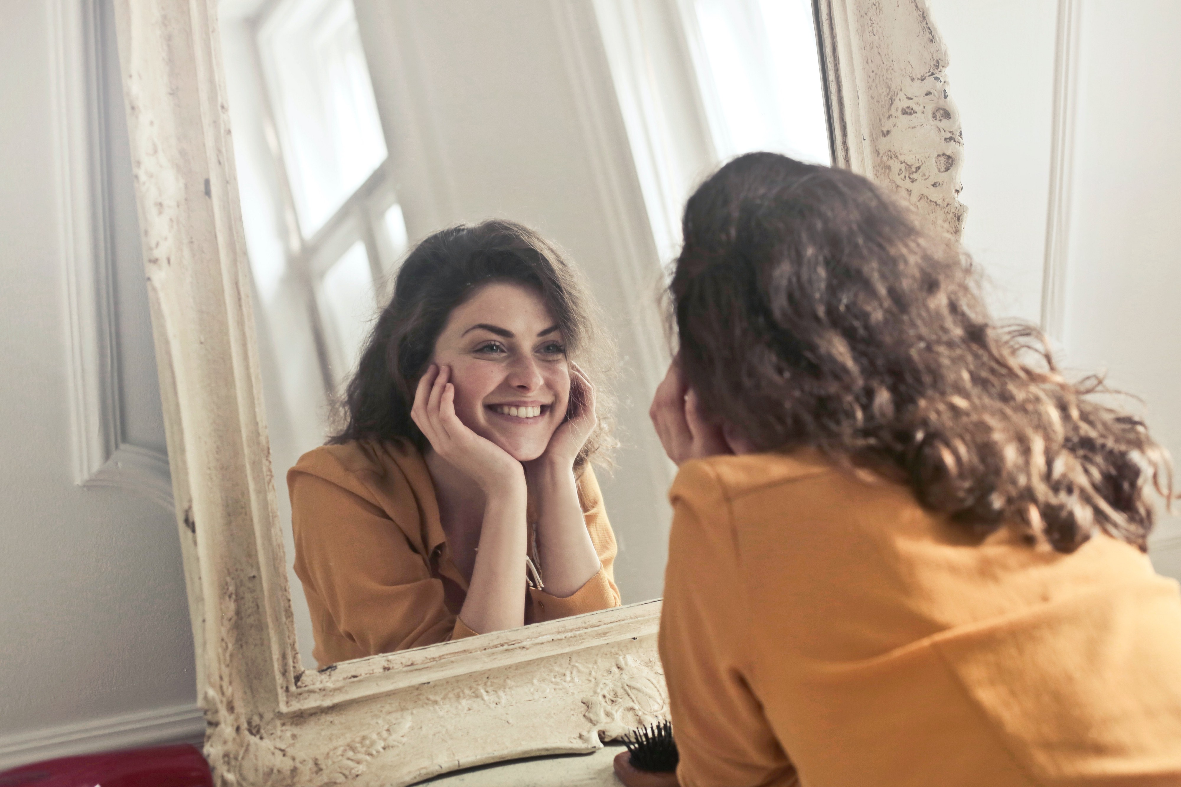 A woman smiles into a mirror.