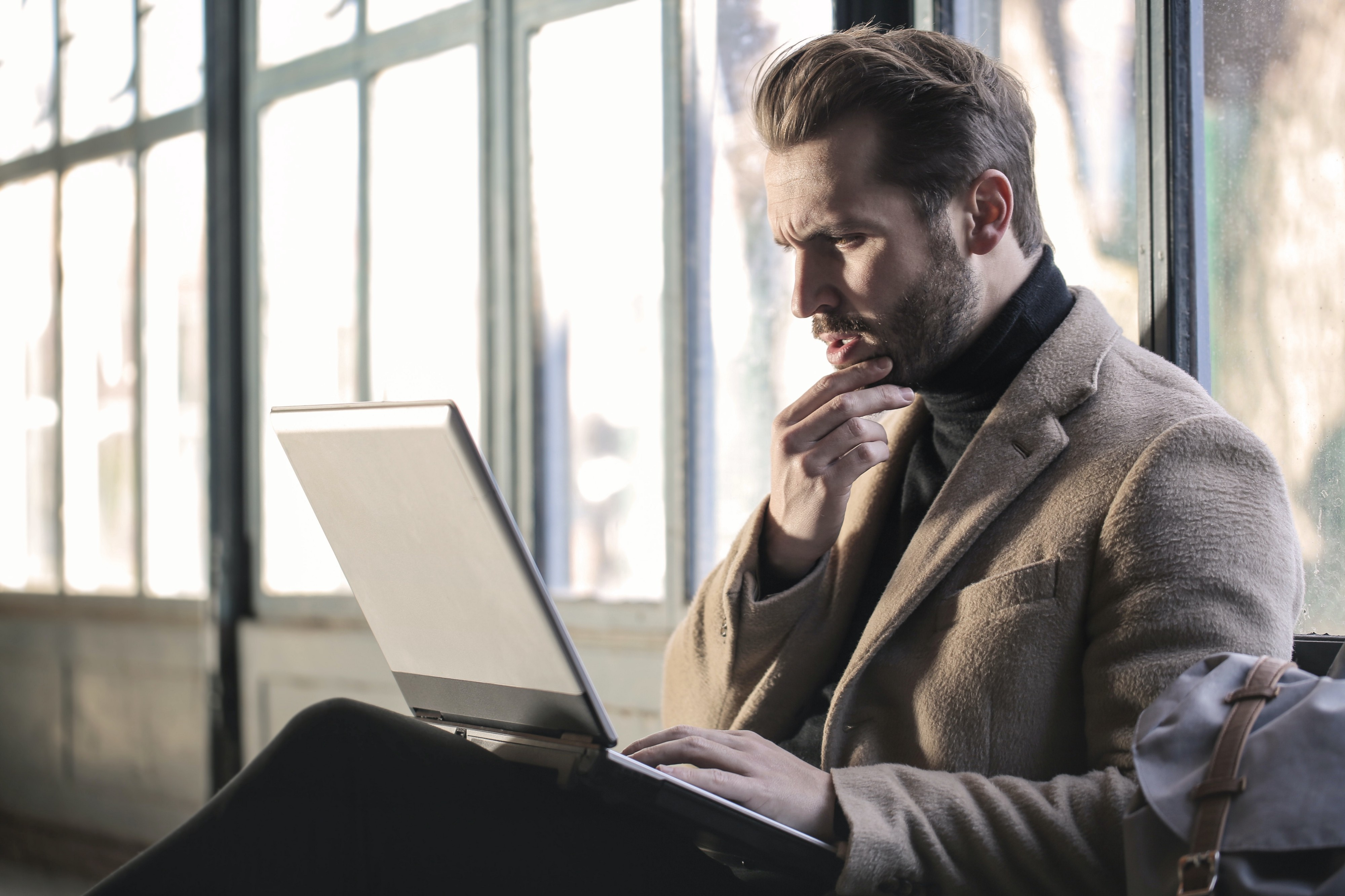 Man sitting and looking at laptop