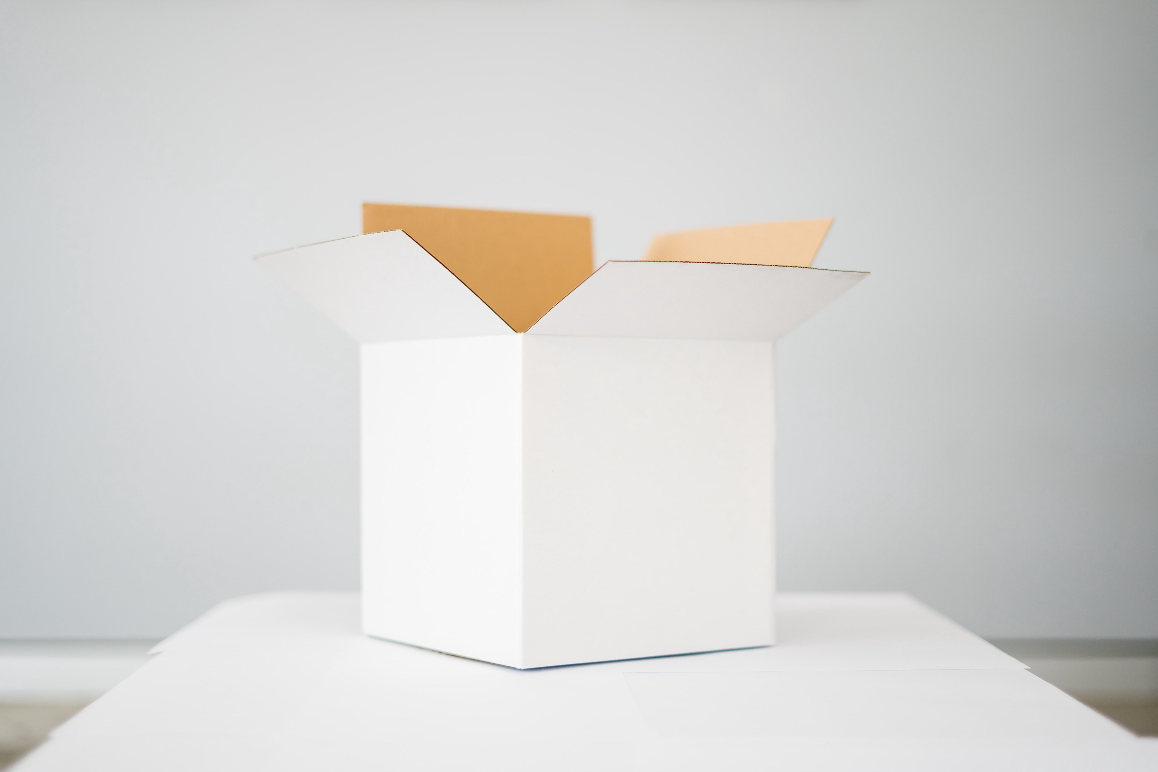 An open, white box placed on a white table.
